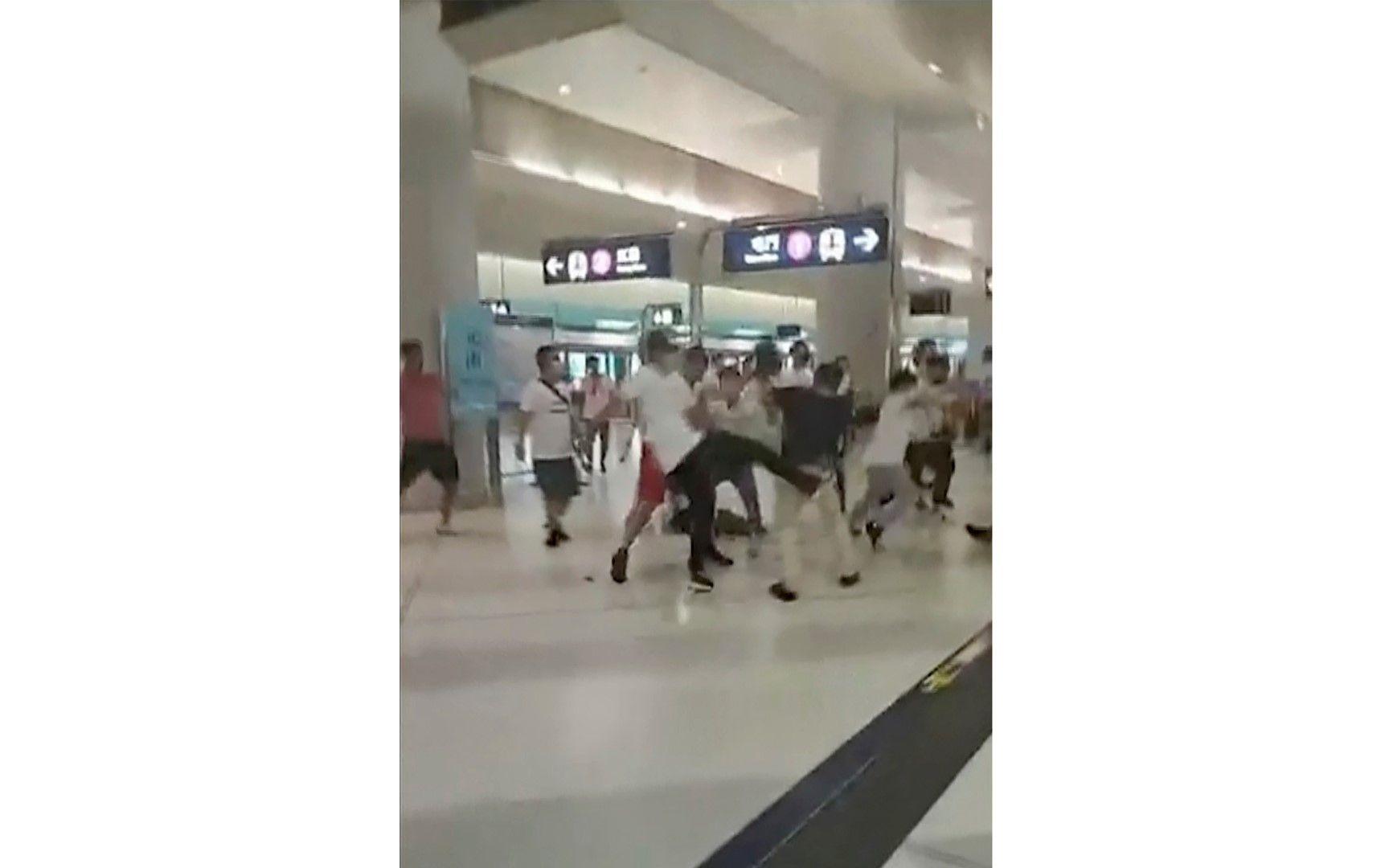 Неделя, 21 юли 2019 г., изображение, взето от видеоклип, показва сблъсък между маскирани нападатели и протестиращи в железопътната гара Юен Лонг в Хонконг