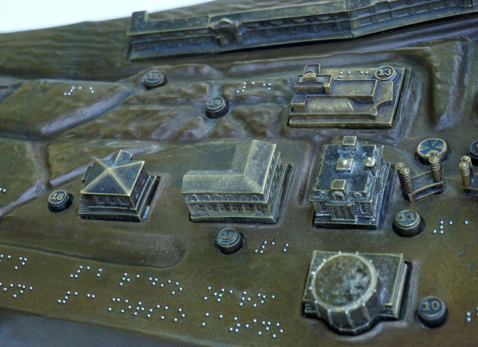 Бронзовата рефелна карта се намира до Слънчевия часовник в Морската градина