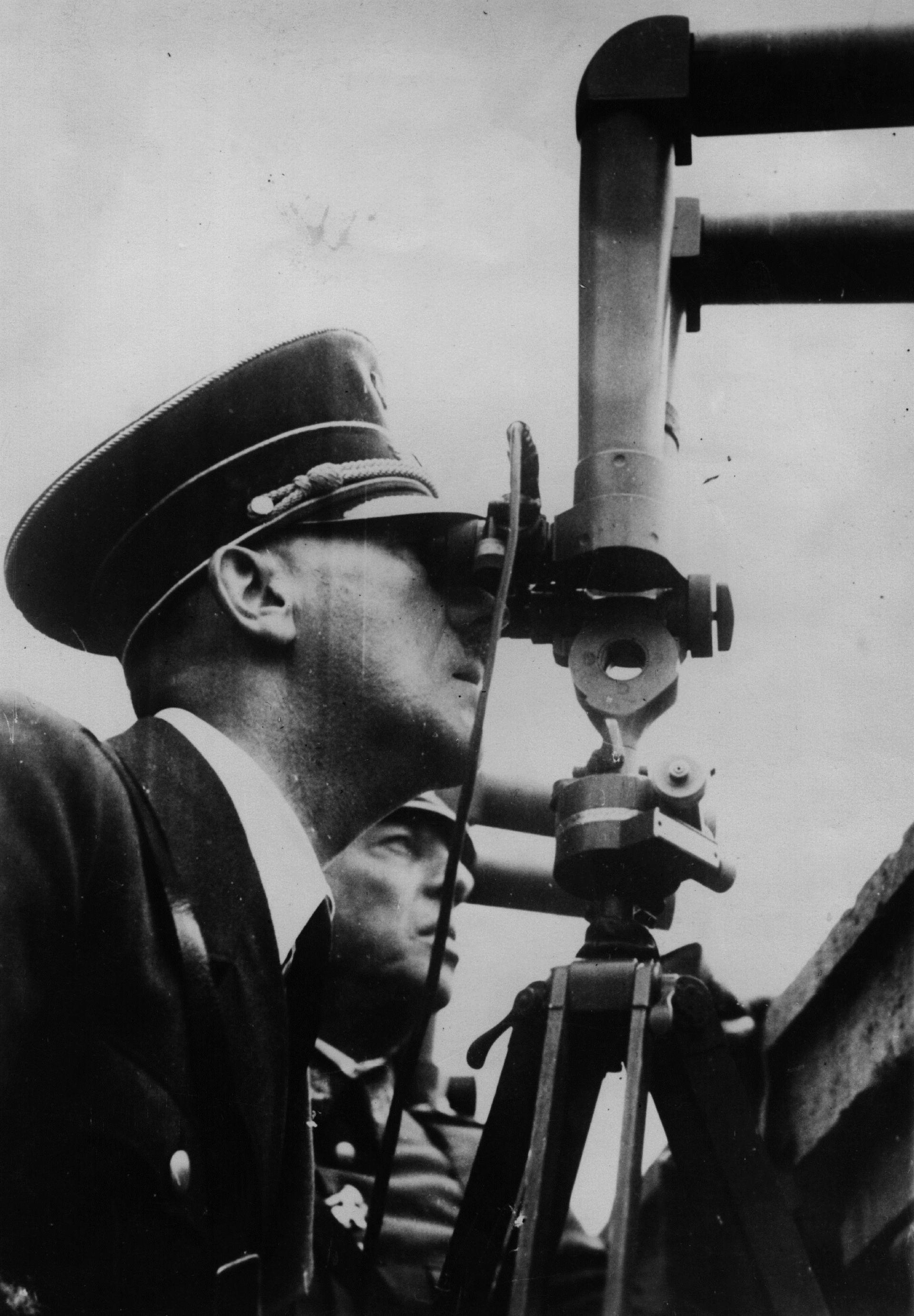 6 октомври 1939 г.: С двете очи, залепени с перископ, германският диктатор Адолф Хитлер (1889 - 1945) злорадства над руините на Варшава