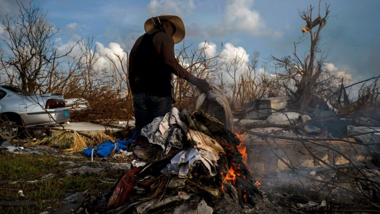 Мери Глинтън изгаря дрехи, повредени от урагана Дориан, на  Бахамските острови.