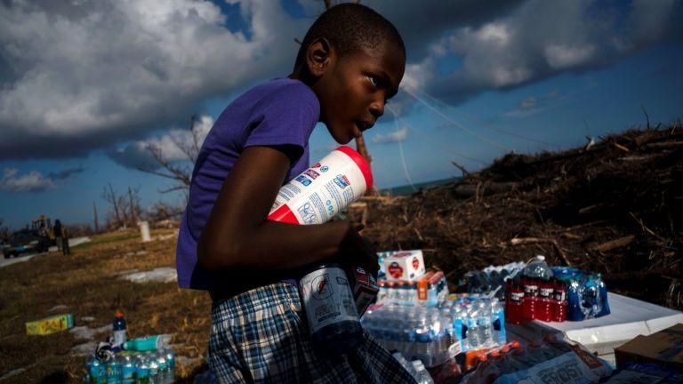 Айфон Минус, 8-годишен, събира дарена храна, която е била донесена с хеликоптер.