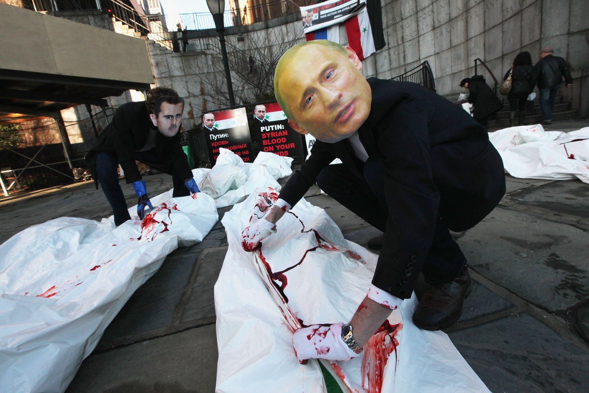24 януари 2011 г. - Актьори с маски на сирийския президент Башар Асад и руския премиер Владимир Путин по време на демонстрация пред централата на Организацията на обединените нации в Ню Йорк. Протестиращите призоваха Съвета за сигурност на САЩ да приеме резолюция, за да спре насилието срещу сирийската опозиция.
