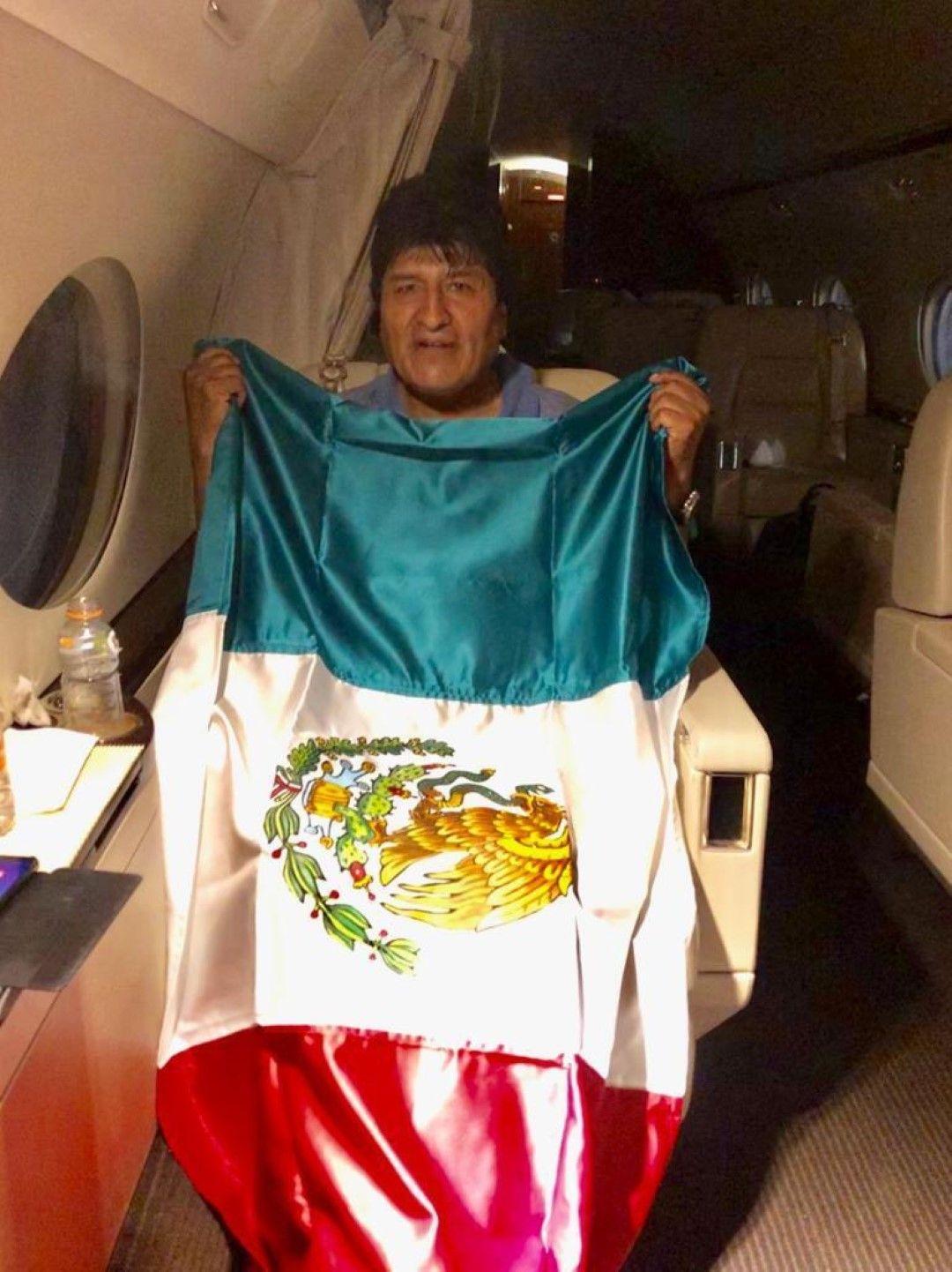 Ево Моралес държи мексиканския флаг на борда на самолета, който го откарва в Мексико. Снимката е направена от външния министър на Мексико Марсело Ебрард