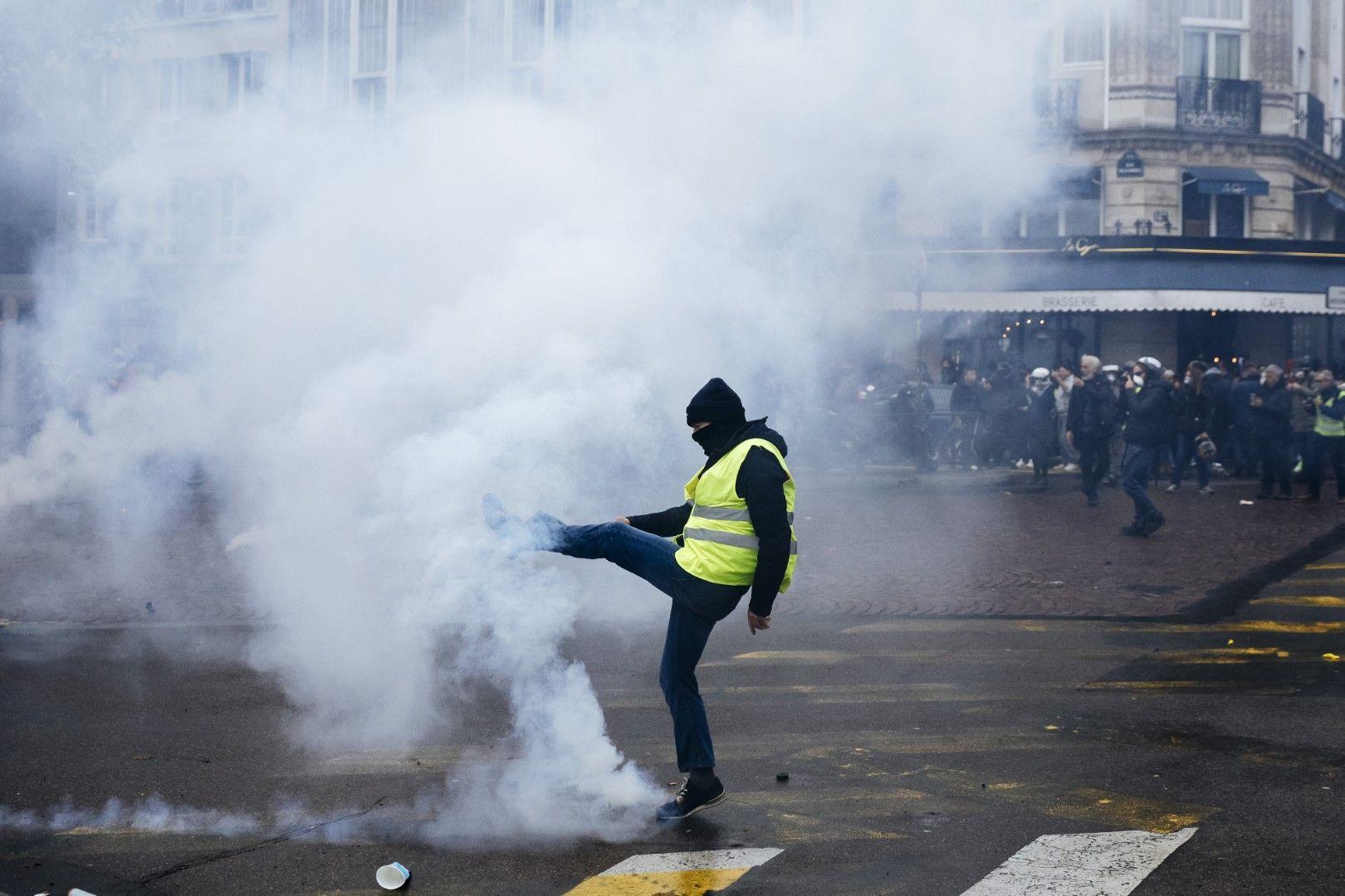 Протестращ изритва флакон със сълзотворен газ по време на протеста в Париж на 16 ноември