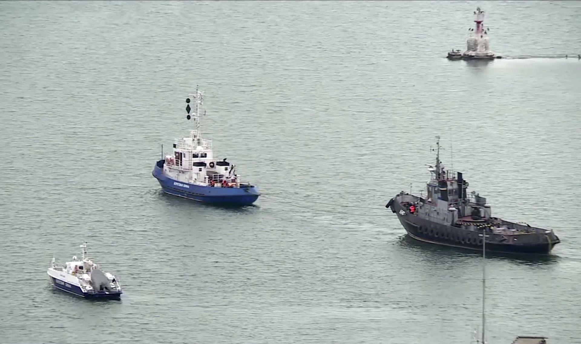 Един от задържаните украински кораба, вляво, теглен от плавателен съд на руската брегова охрана в Керч