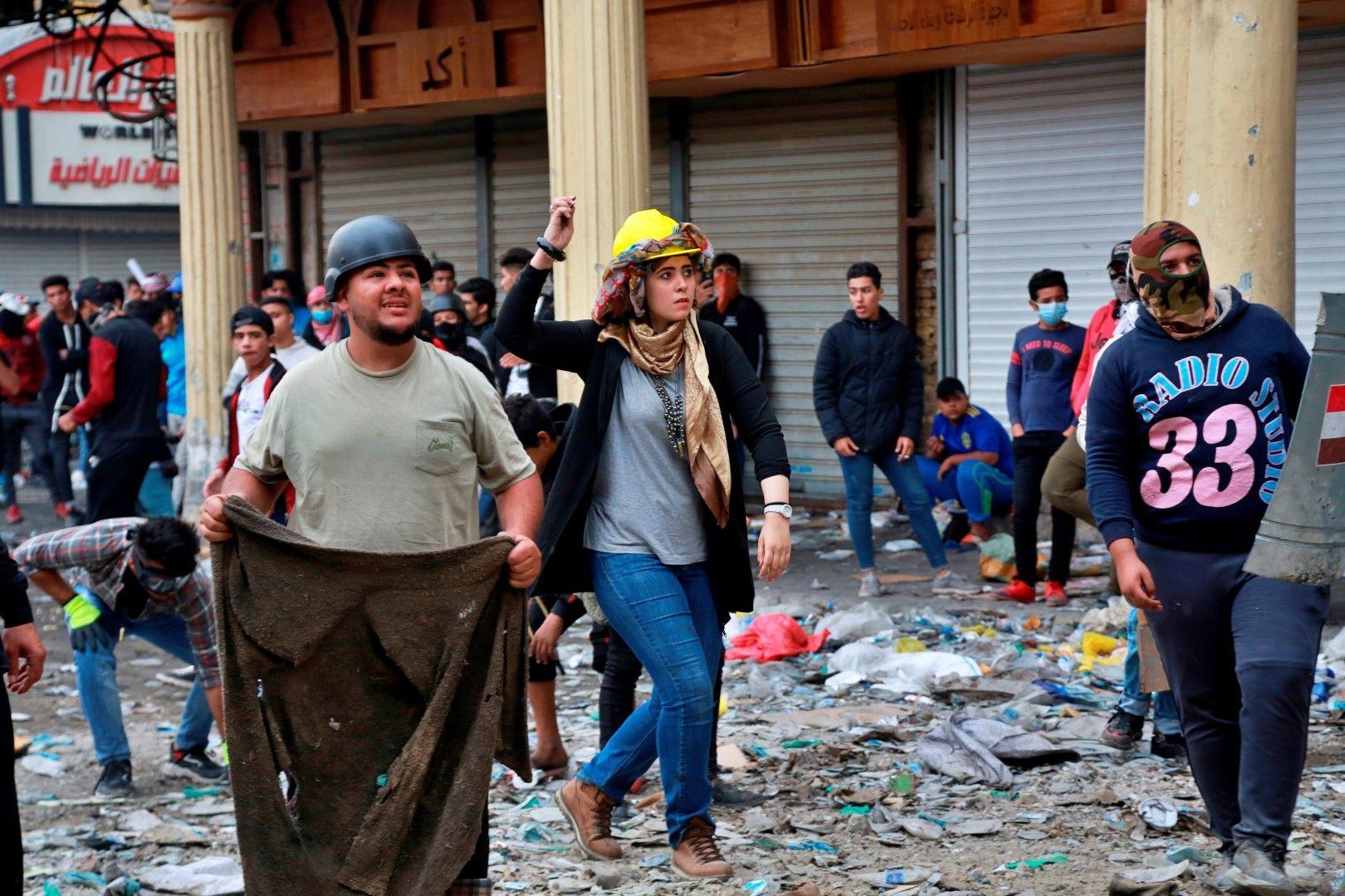Протестиращи хвърлят камъни по полицията при антиправителствен протест в Багдад, 28 ноември