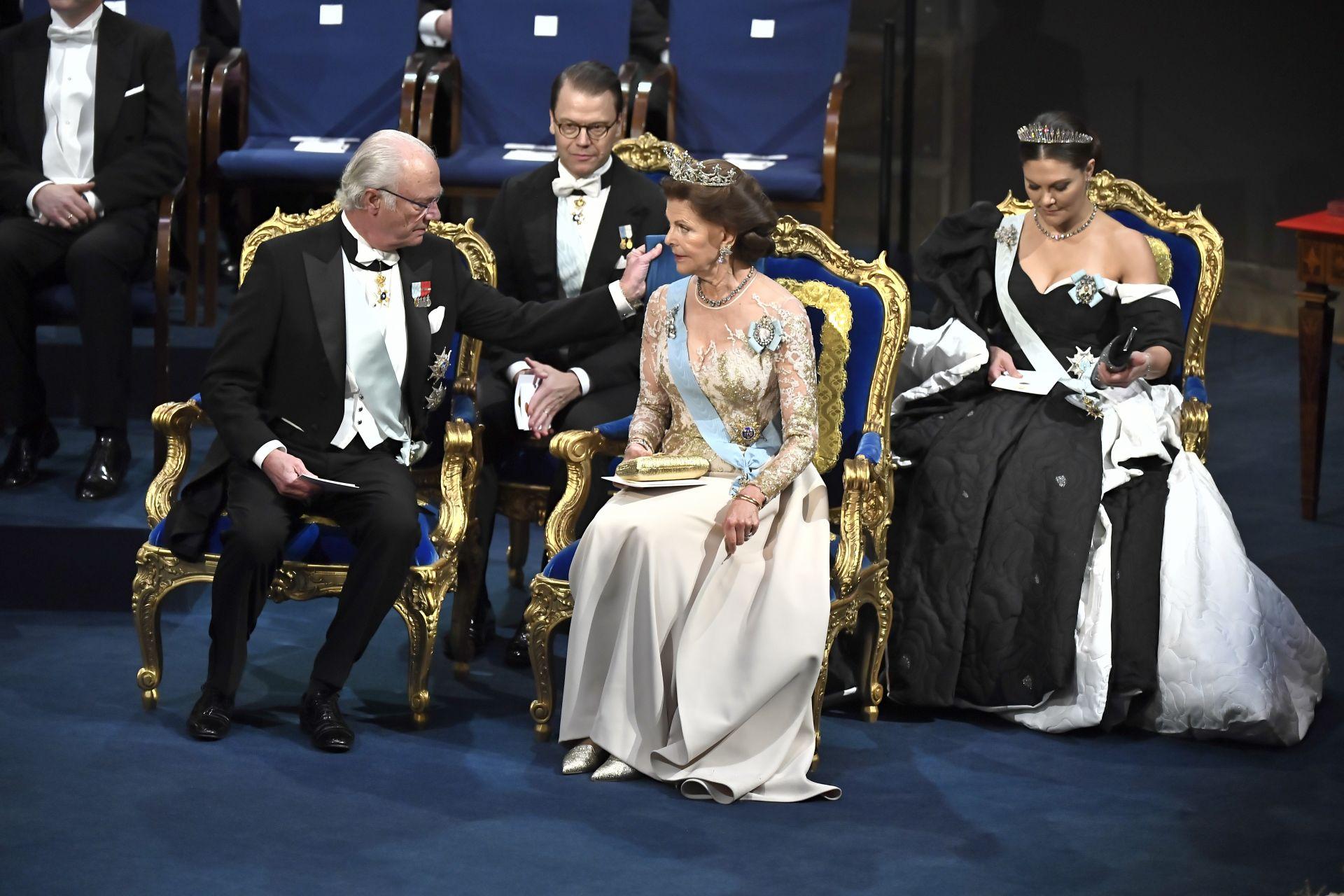 Кралят на Швеция Карл Густаф оправя възглавница на кралица Силвия на церемонията по награждаването на Нобел в Концертната зала в Стокхолм