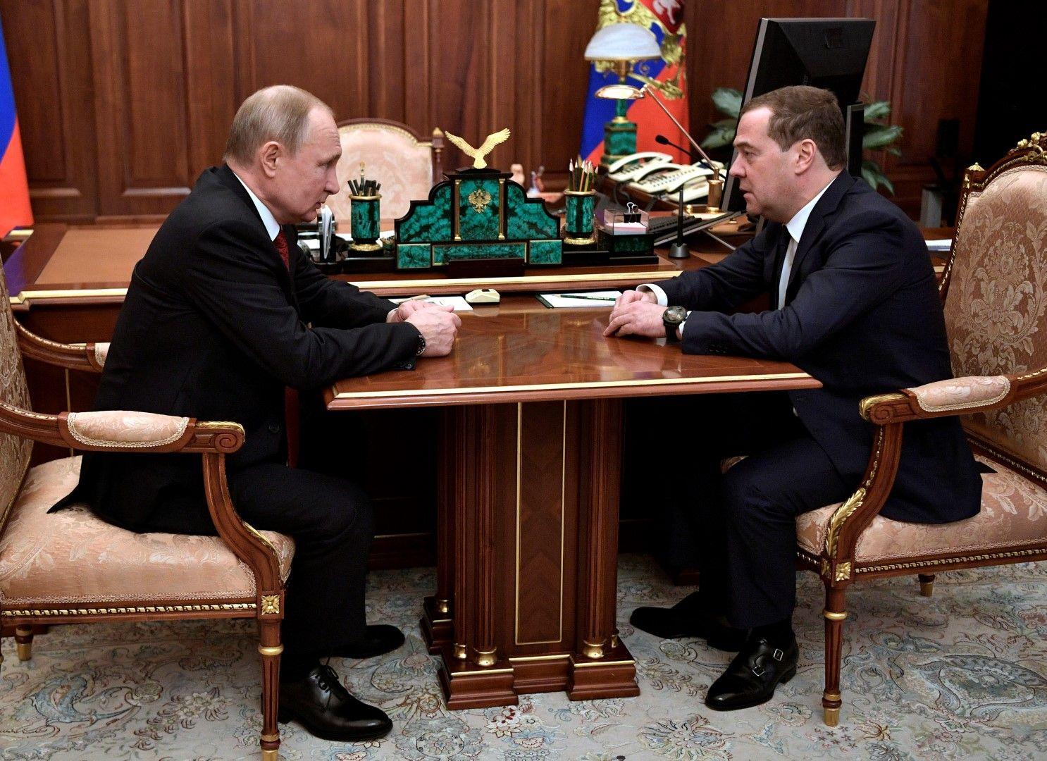 Владимир Путин изслушва Дмитрий Медведев по време на срещата им в Кремъл днес, 15 януари