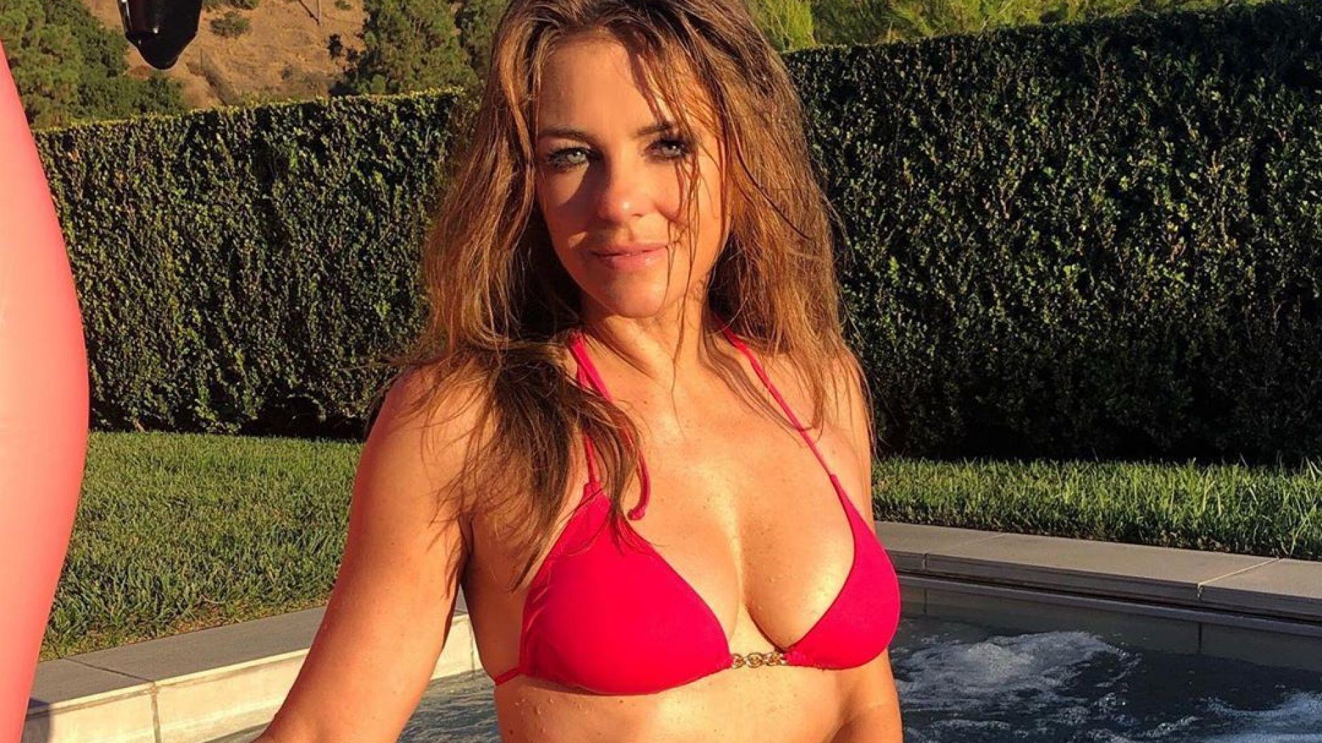 Изкушение в цикламено: На 54 Елизабет Хърли показа перфектна фигура по бански