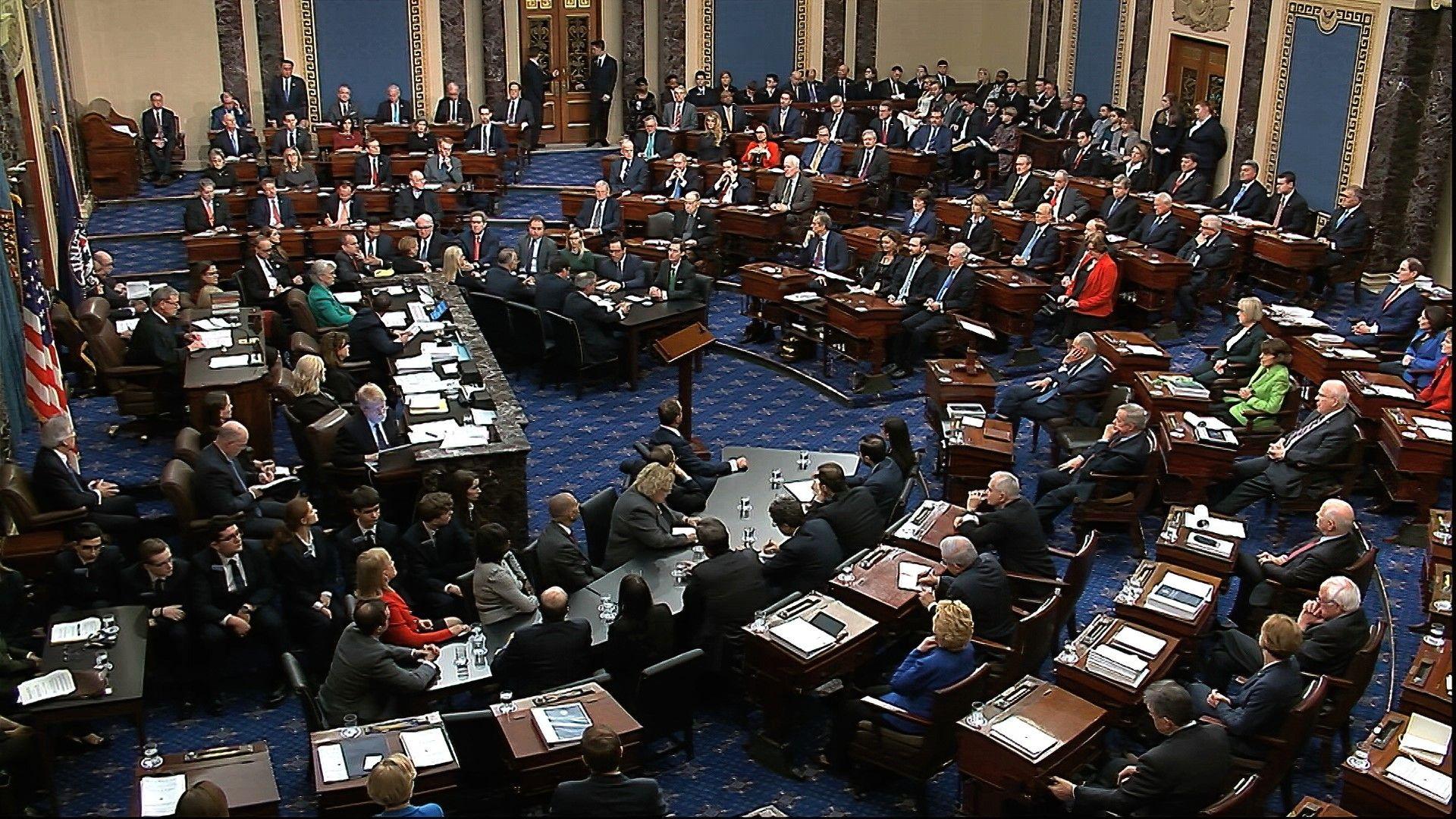 Снимка, направена от видео, показва Мит Ромни, вторият отляво на последния ред, изправен, се изказва пред сенаторите преди да гласува против Тръмп по първото обвинение - злоупотреба с власт