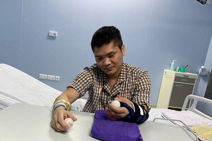 Пациентът държи топка за пинг-понг в двете си ръце, докато се възстановява с трансплантираната си лява ръка