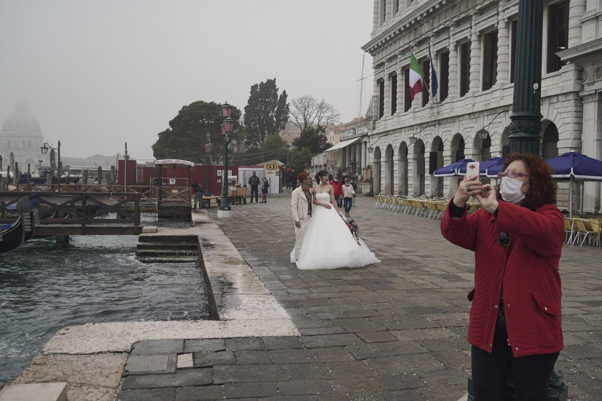Младоженка позира за снимки, докато туристите носят защитни маски във Венеция