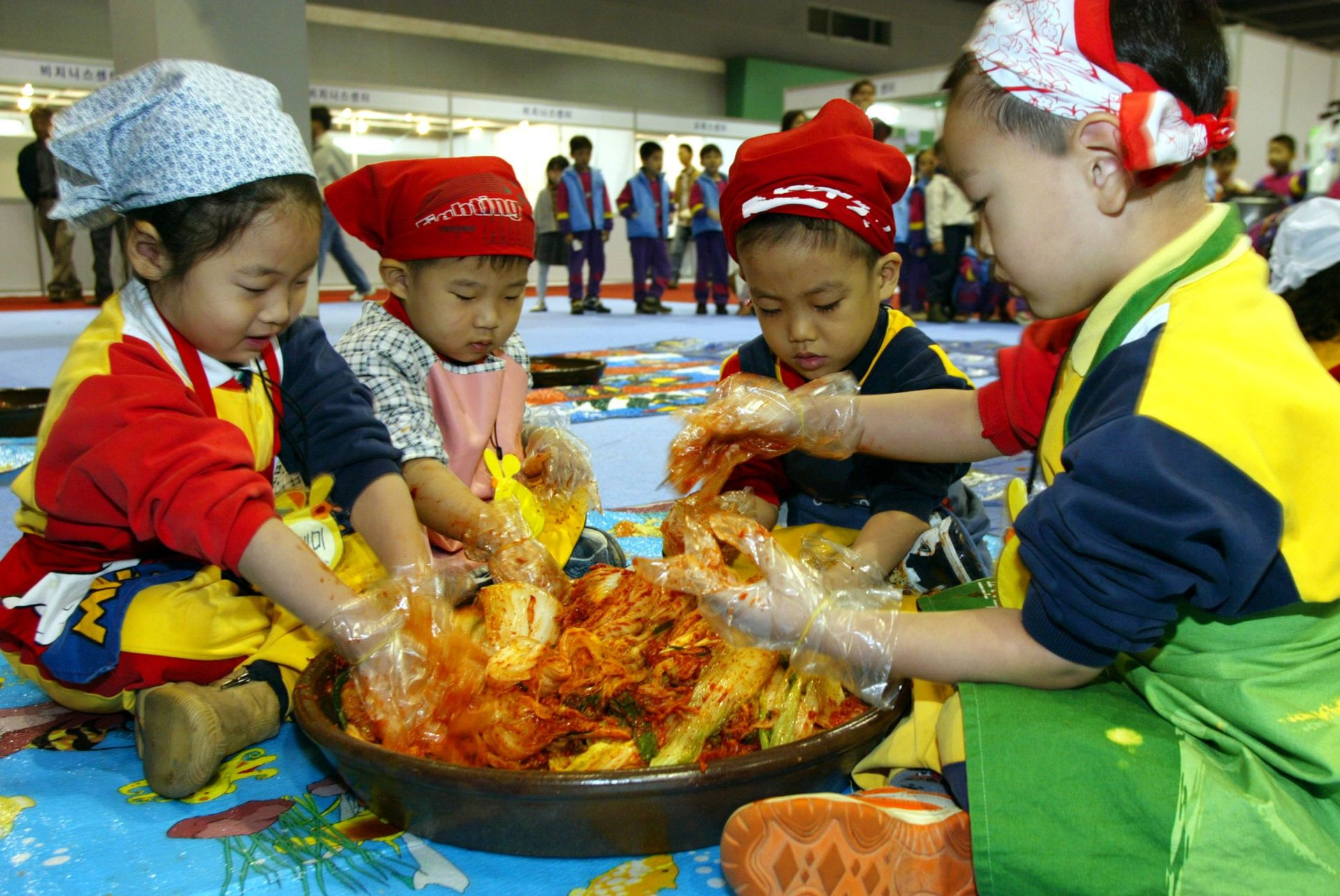 Южнокорейските деца правят националното ястие кимчи на изложение на 6 ноември 2003 г. в Сеул. По това време ястието е търсено в Източна Азия заради убеждението, че може да предпази от SARS