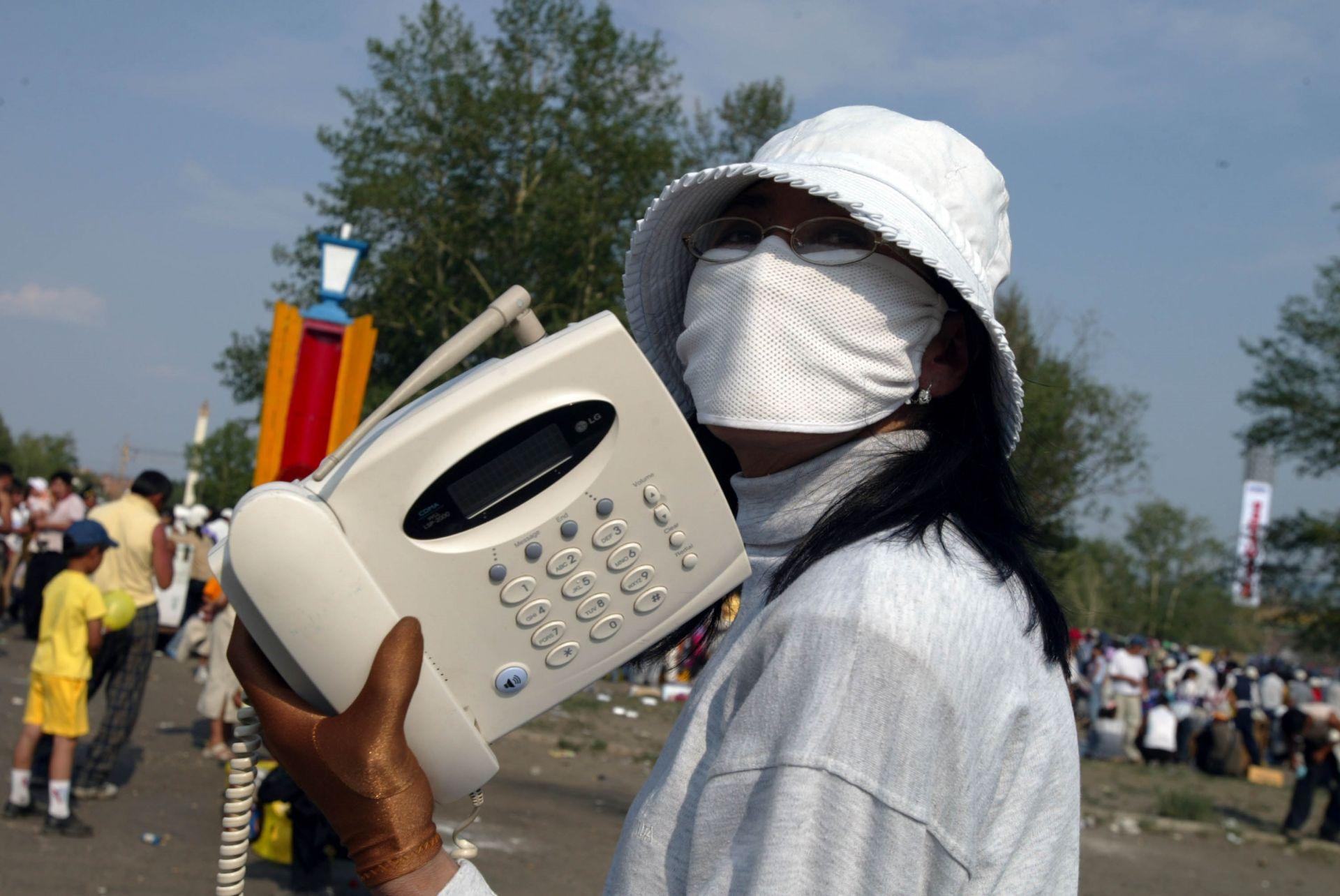 15 юли 2003 г. в Улан Батор, Монголия: Предприемчив монголски телефонен оператор носи защитни маска за лице и ръкавици срещу SARS, докато чака клиентите да използват телефона