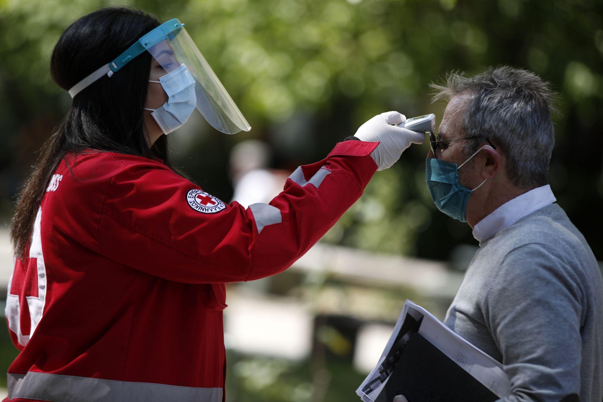 Медицински работник мери температурата, на влизащите в съдилищата в Гърция, които бяха отворени във вторник