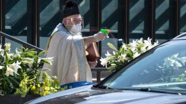 Свещеник с воден пистолет пръска миряни със светена вода, за да спазва дистанция