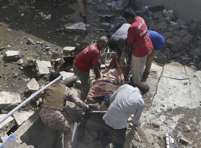 Местни хора пренасят тялото на една от жертвите