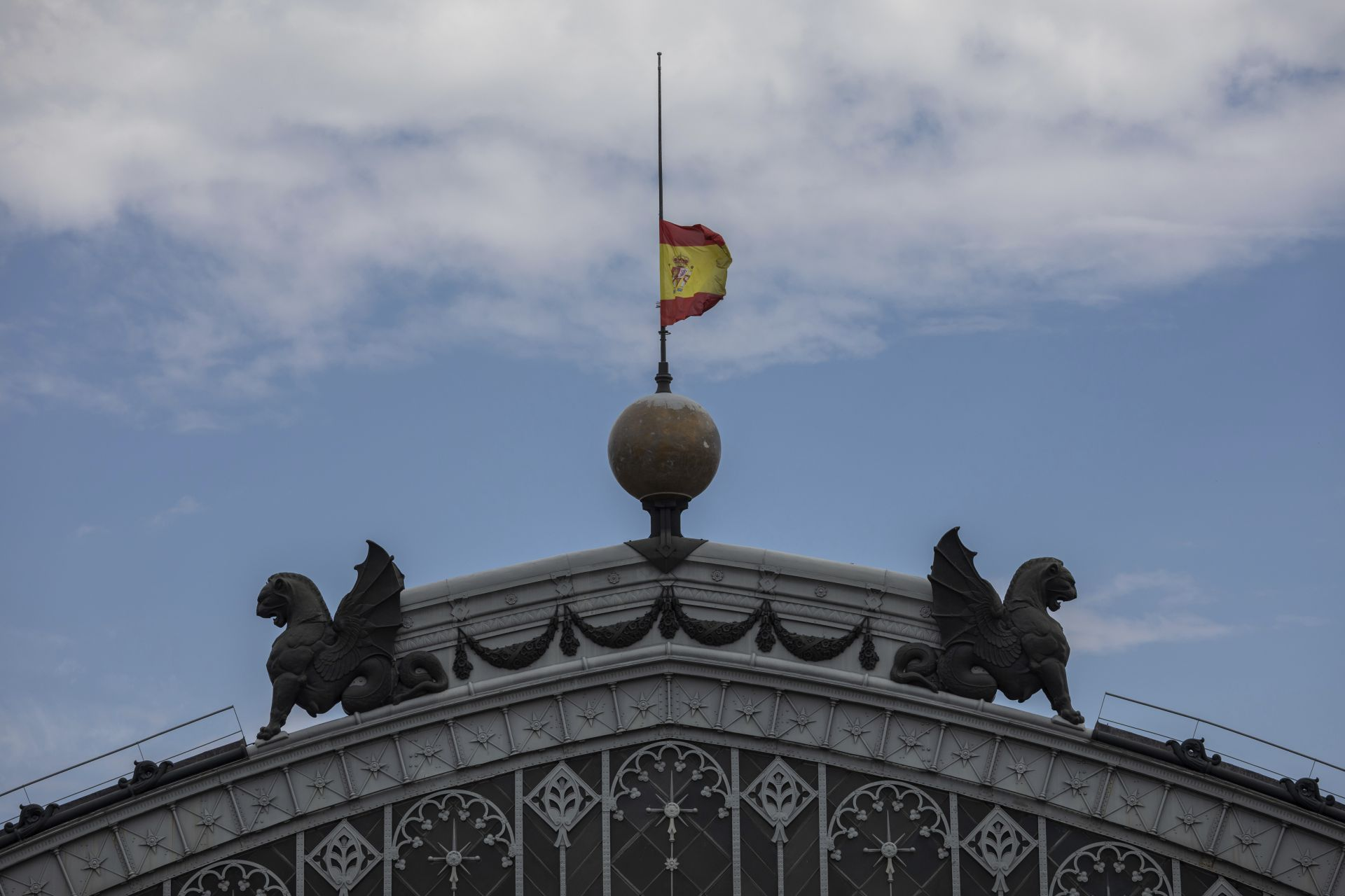Испански флаг, свален на половината над купола на жп гара в Мадрид в памет на жертвите на COVID-19 в страната
