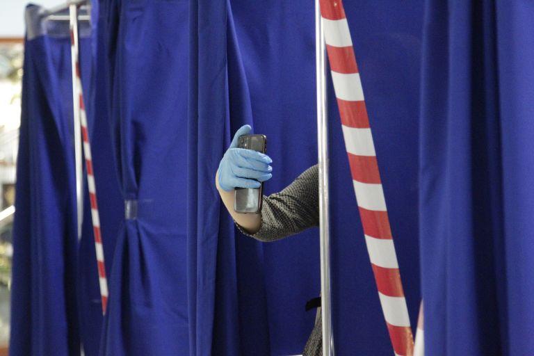 Жена прави селфи, преди да подаде бюлетината си в избирателна секция с портрети на руския президент Владимир Путин  чеченския регионален лидер Рамзан Кадиров в Грозни