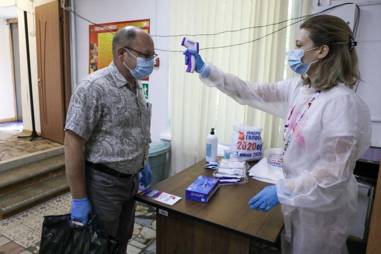 Член на изборната комисия, вдясно, проверява температурата на избирателя в Москва