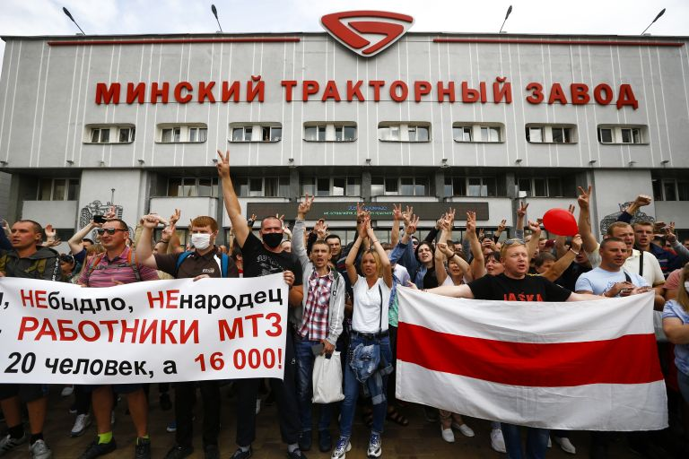 """Работниците държат банер с надпис """"ние не сме говеда, не сме овце, ние сме работници на МТЗ, не сме 20 души, ние сме 16 000"""", докато те маршират по време на митинг край Минския завод за трактори"""