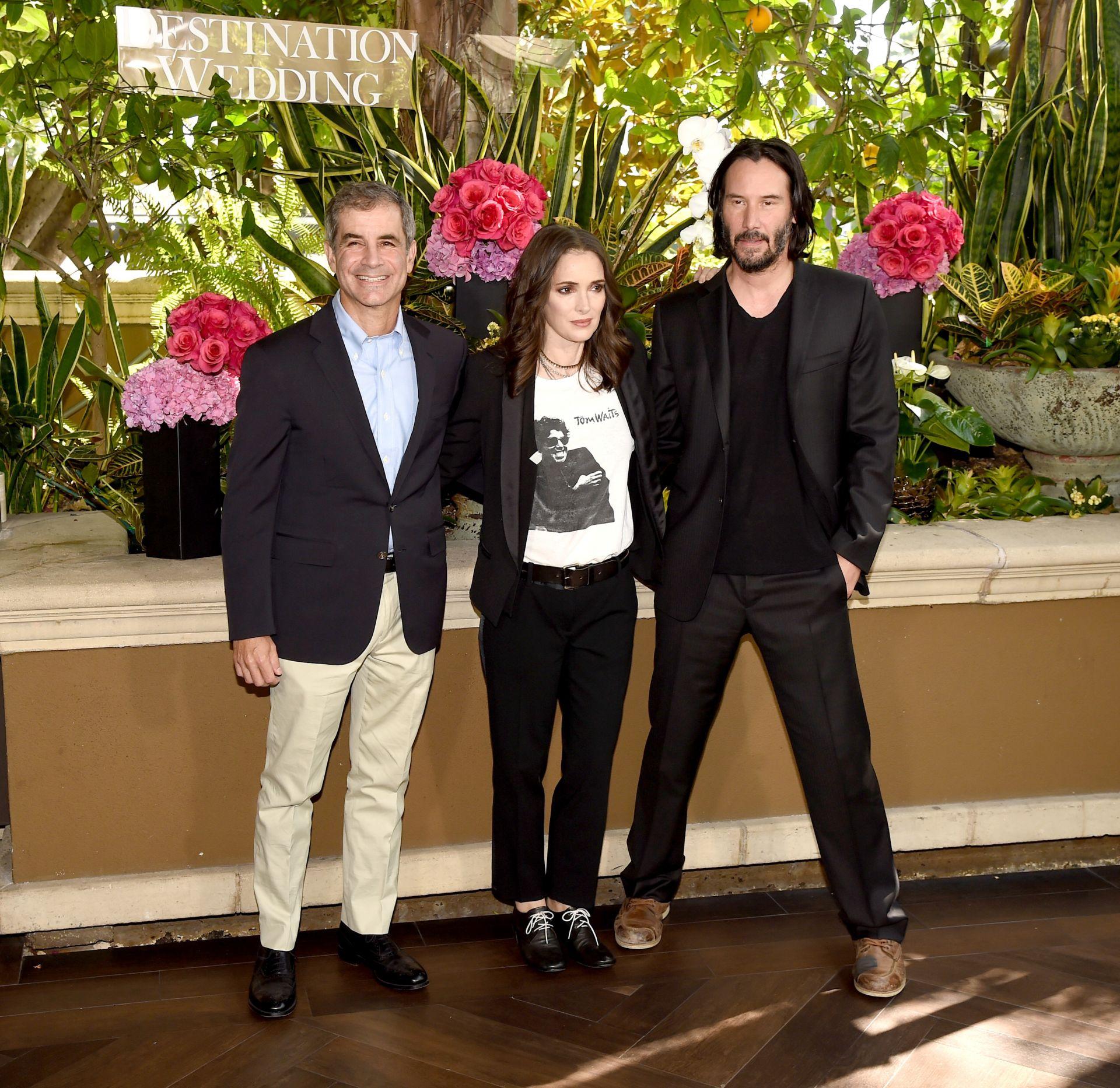 Любимите блейзър, тениска, обувки с връзки и Киану Рийвс от лявата ѝ страна
