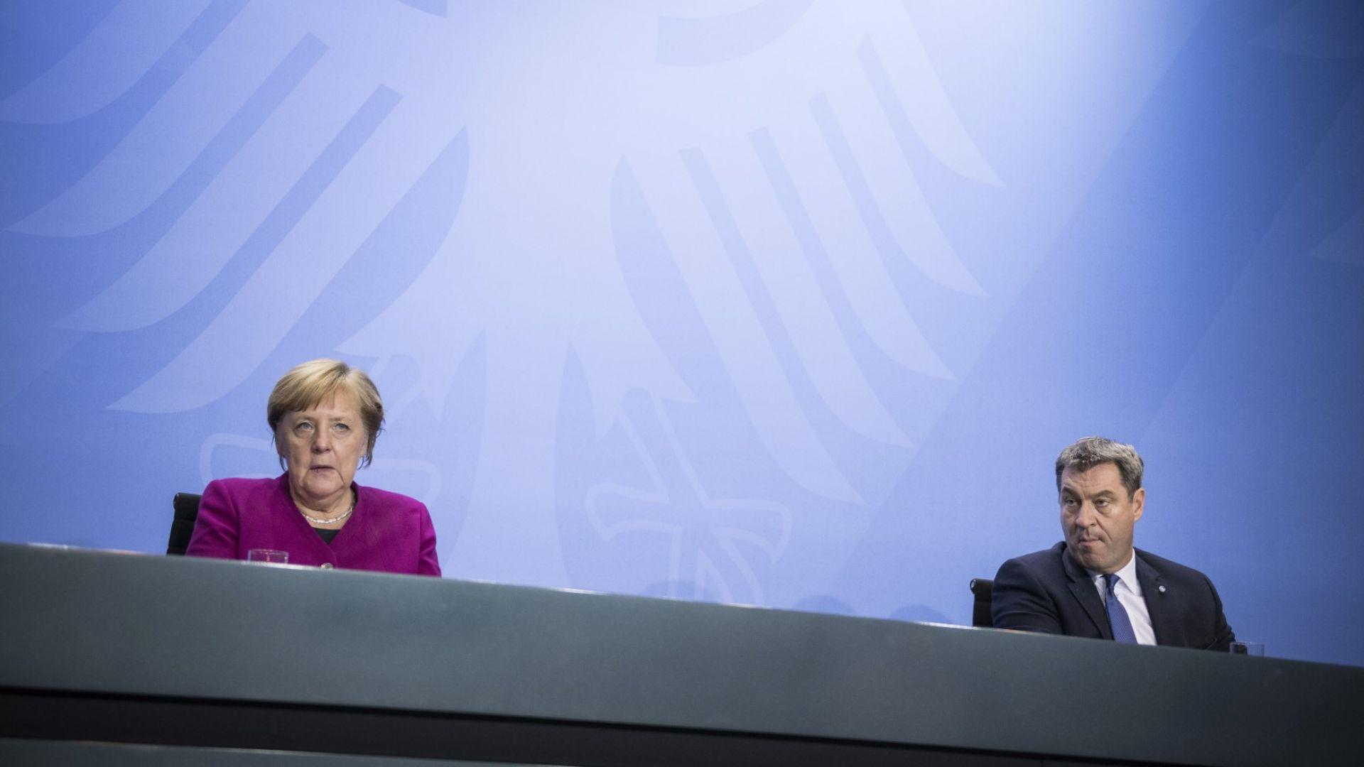 Ангела Меркел и премиерът на провинция Бавария Маркус Зьодер - един до друг, но и на разстояние поне 1.5 метра, по време на заседанието на ръководителите на провинции
