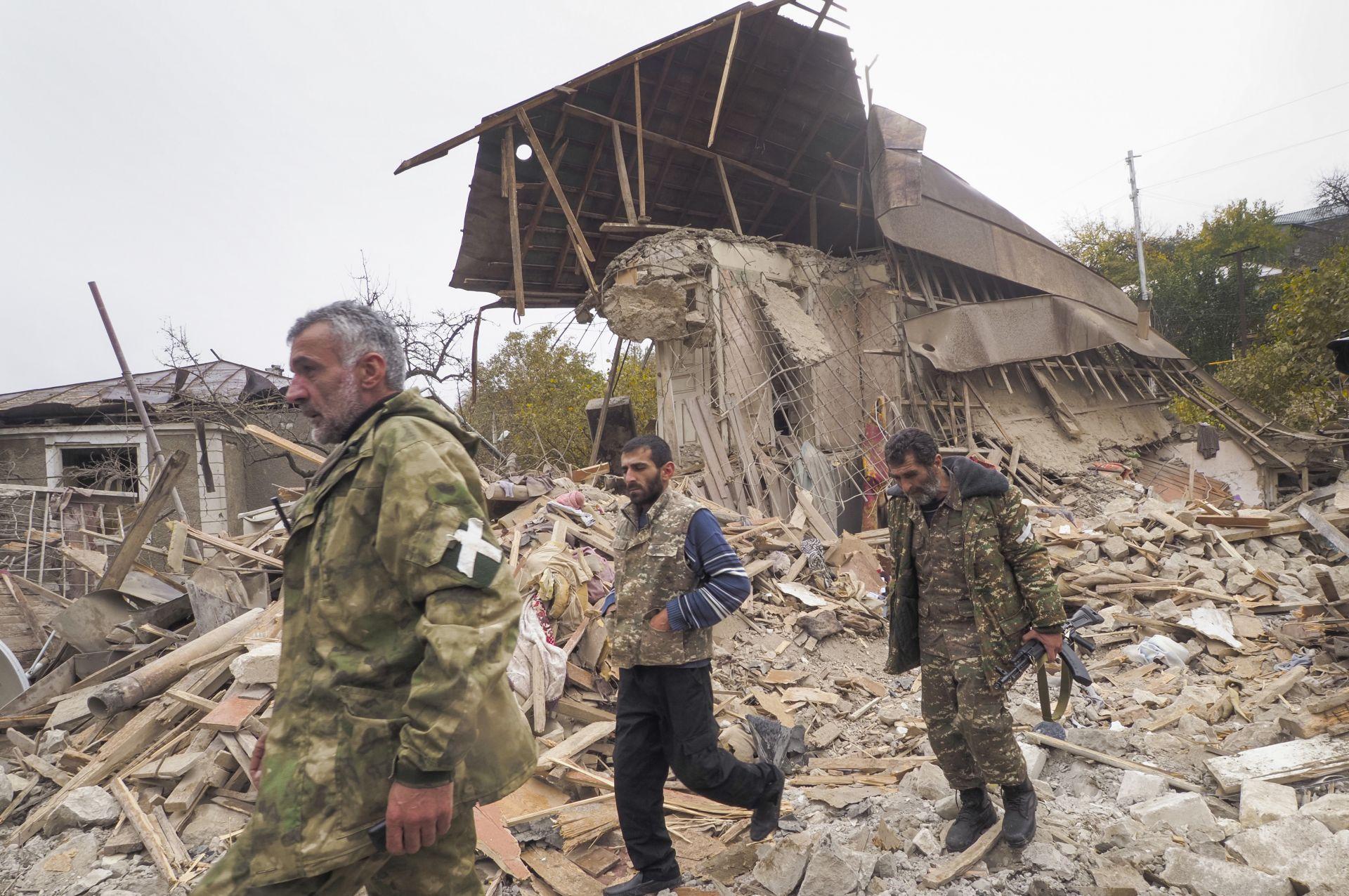 Етнически арменски войници минават покрай къща, разрушена от обстрела от азербайджанската артилерия в Степанакерт