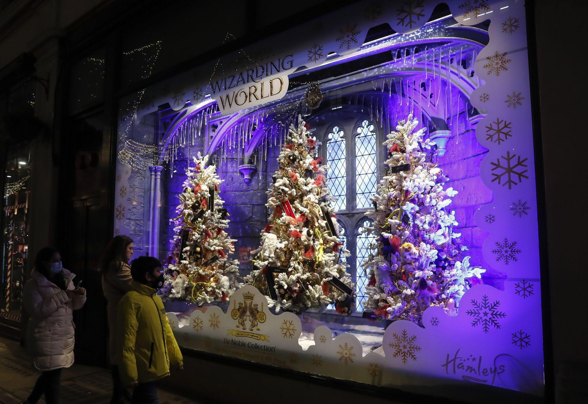 Хора минават покрай витрина с коледни украси в централен Лондон