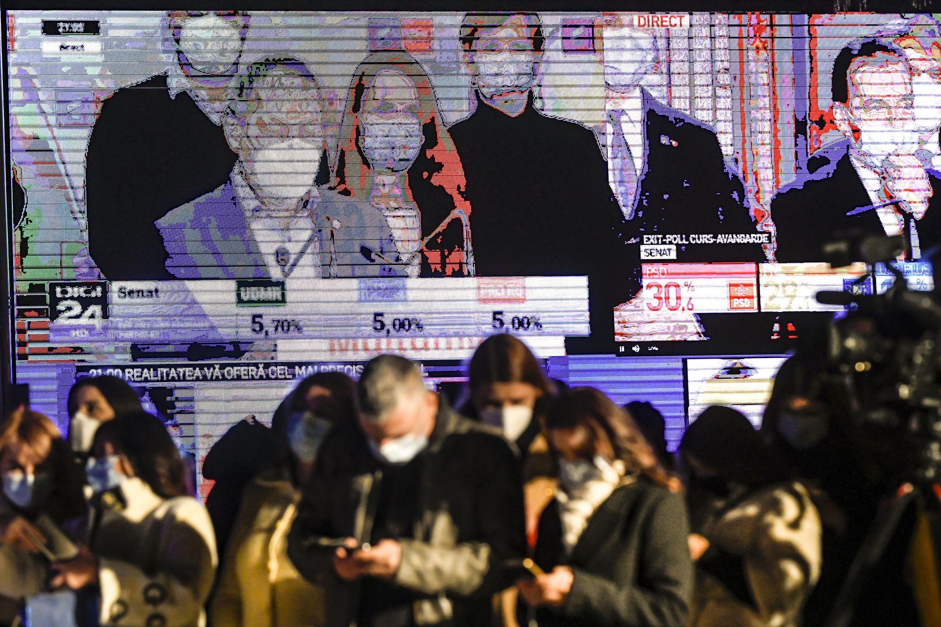 Журналисти следят резултатите през мобилните си устройства на фона на голяма видео стена