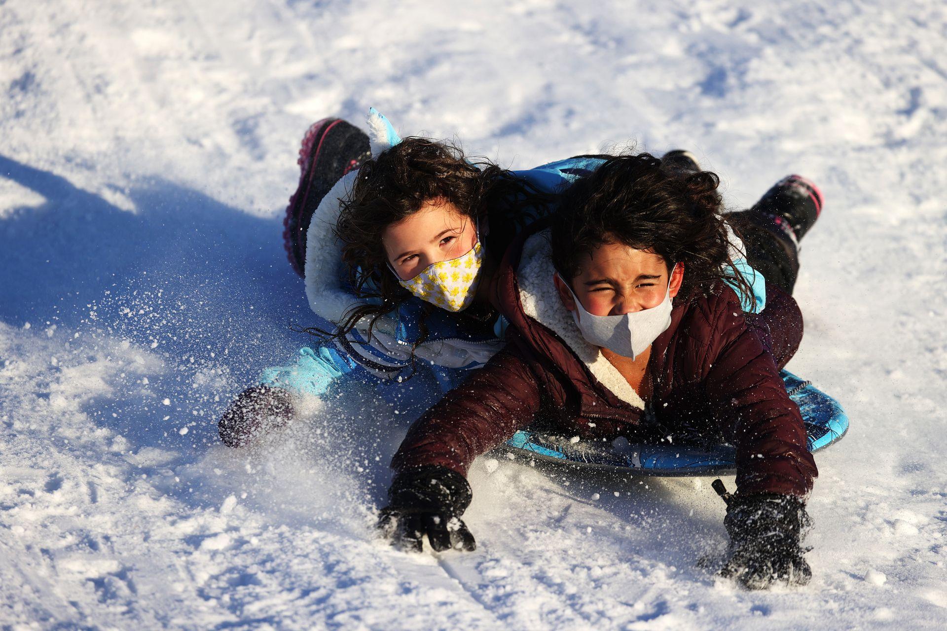 Деца се спускат с шейни след снежната буря