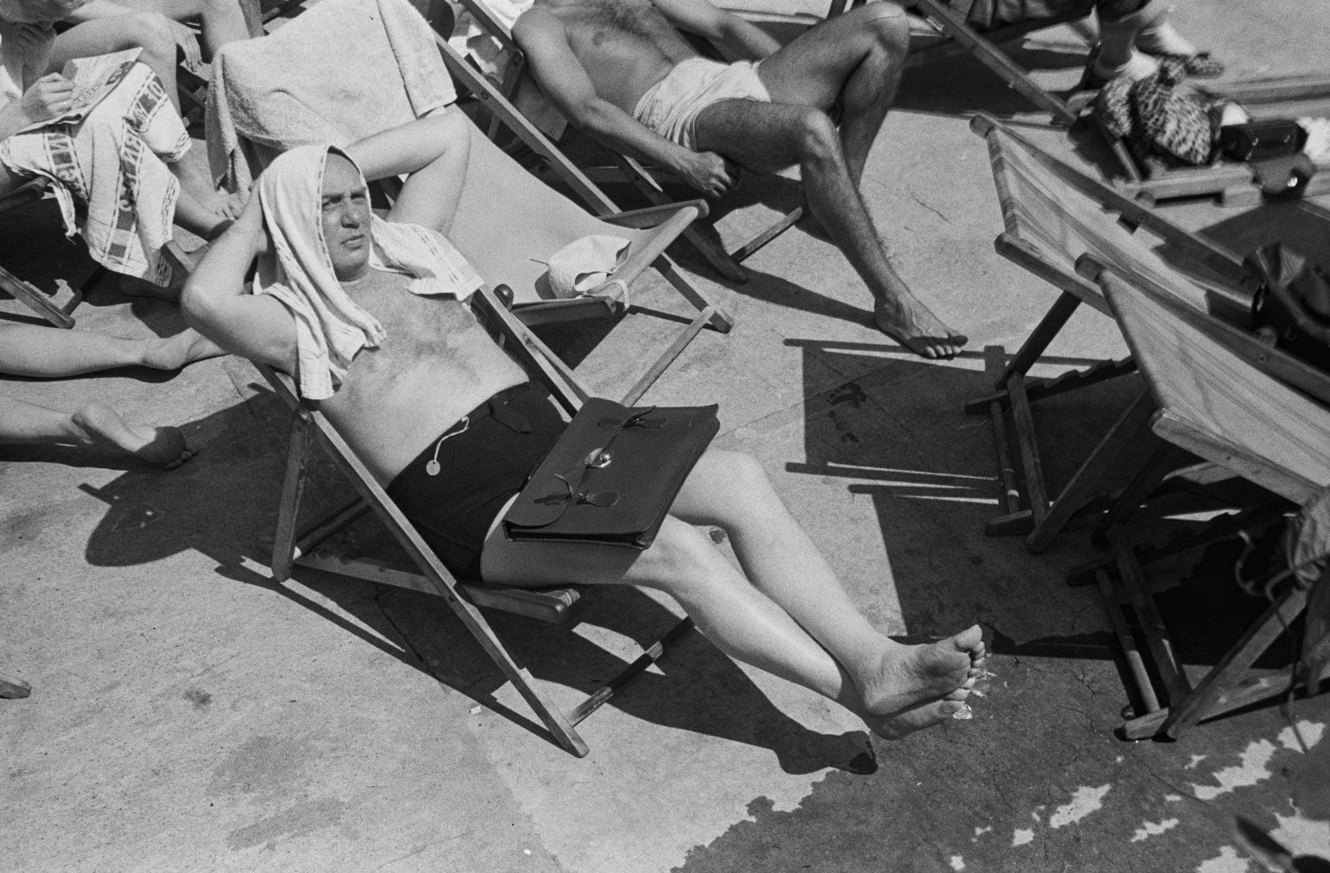 Мъж под слънчевите лъчи, докато се пе покрай басейн, разположен на покрива на лондонска сграда  Снимка: Грейс Робъртсън