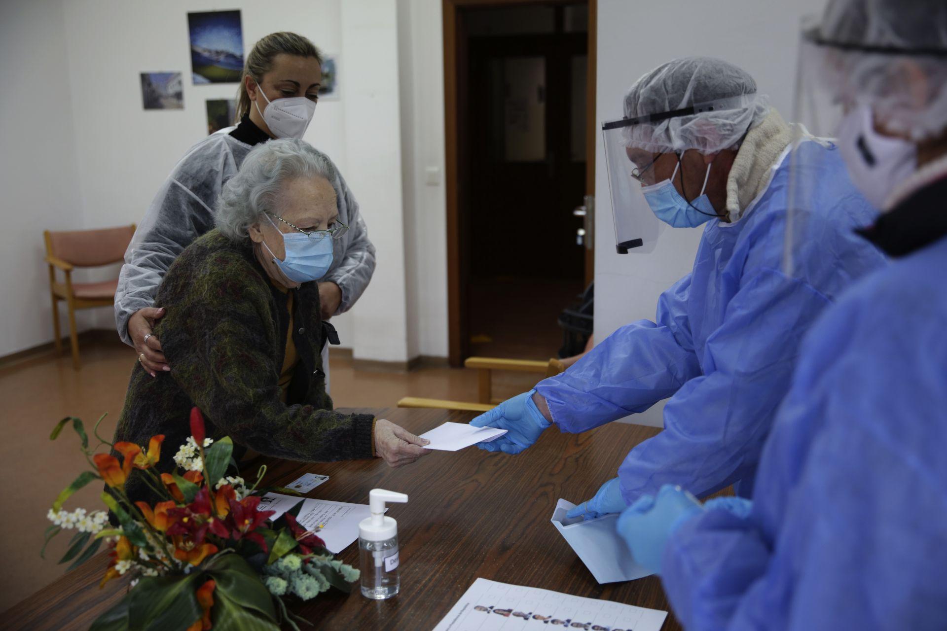89-годишната Роза Гордо връчва бюлетината си за президентски избори на общински служители в защитно облекло в дома за възрастни хора, където тя живее в Монтихо