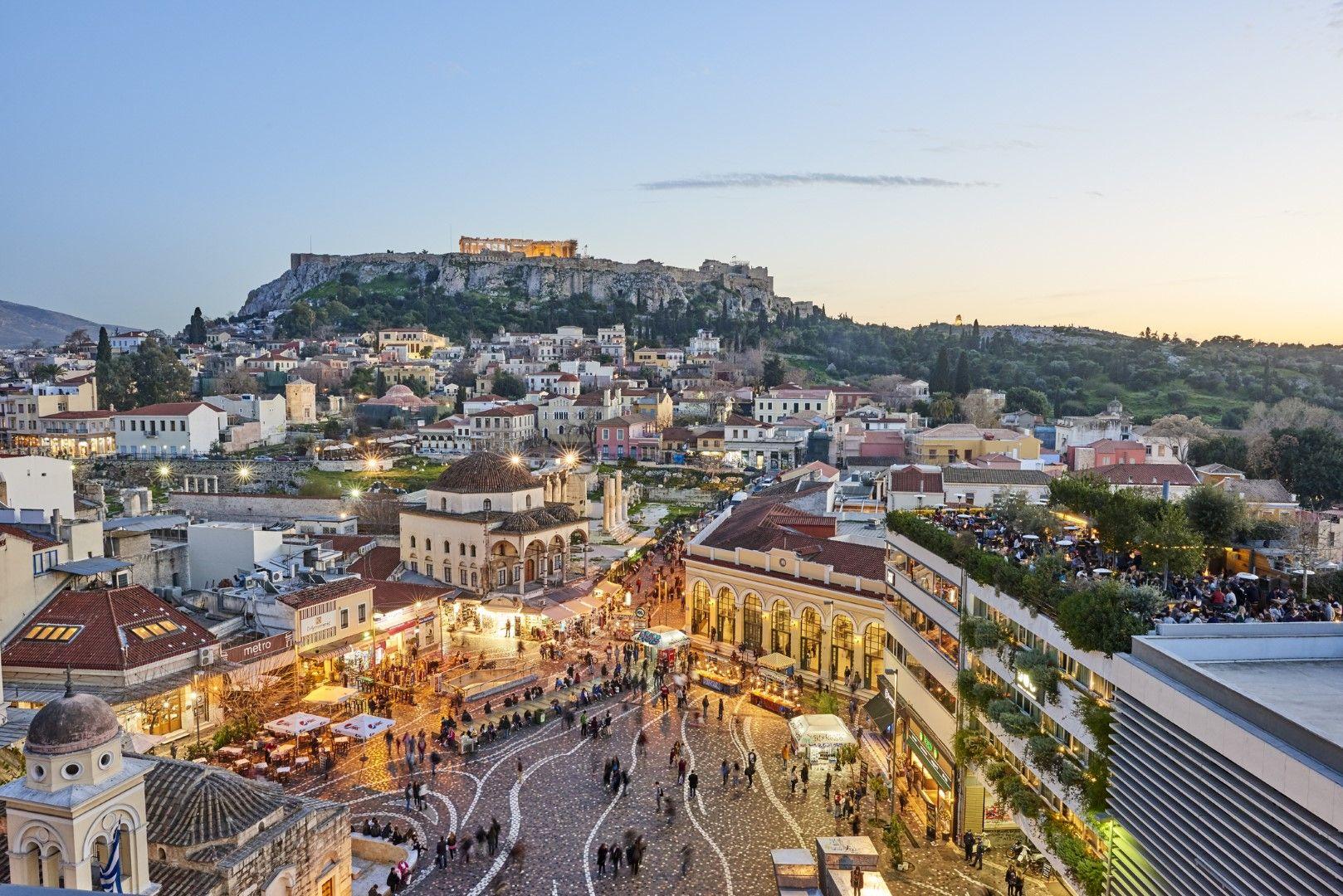 Гледка към площад Монастираки, къщите на Плака и осветения Акропол на хълма по залез., Атина.
