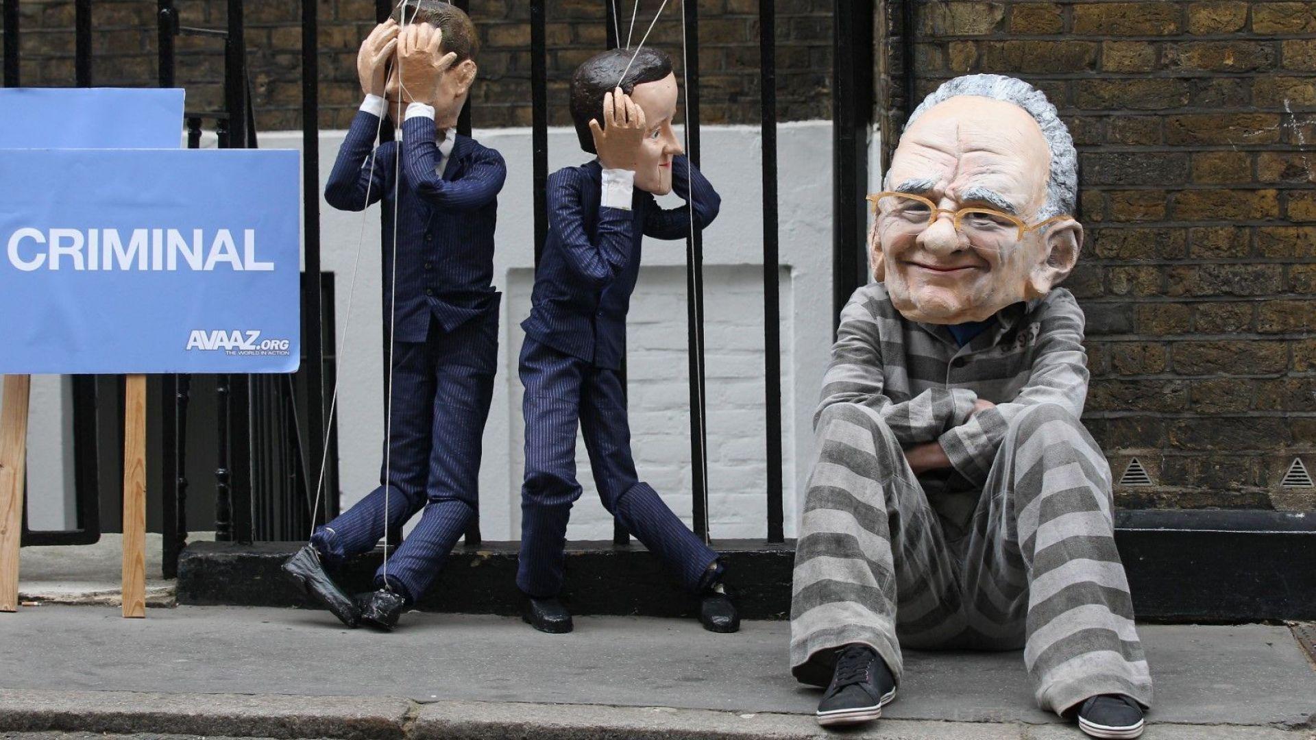Протестиращ с маска на Рупърт Мърдок демонстрира с кукли на политическите лидери на консерваторите и лейбъристите - Дейвид Камерън и Ник Клег, пред апартамента на изпълнителния директор на News Corp на 13 юли 2011 г. покрай скандала с хакването на телефона на тийнейджър от News of the World