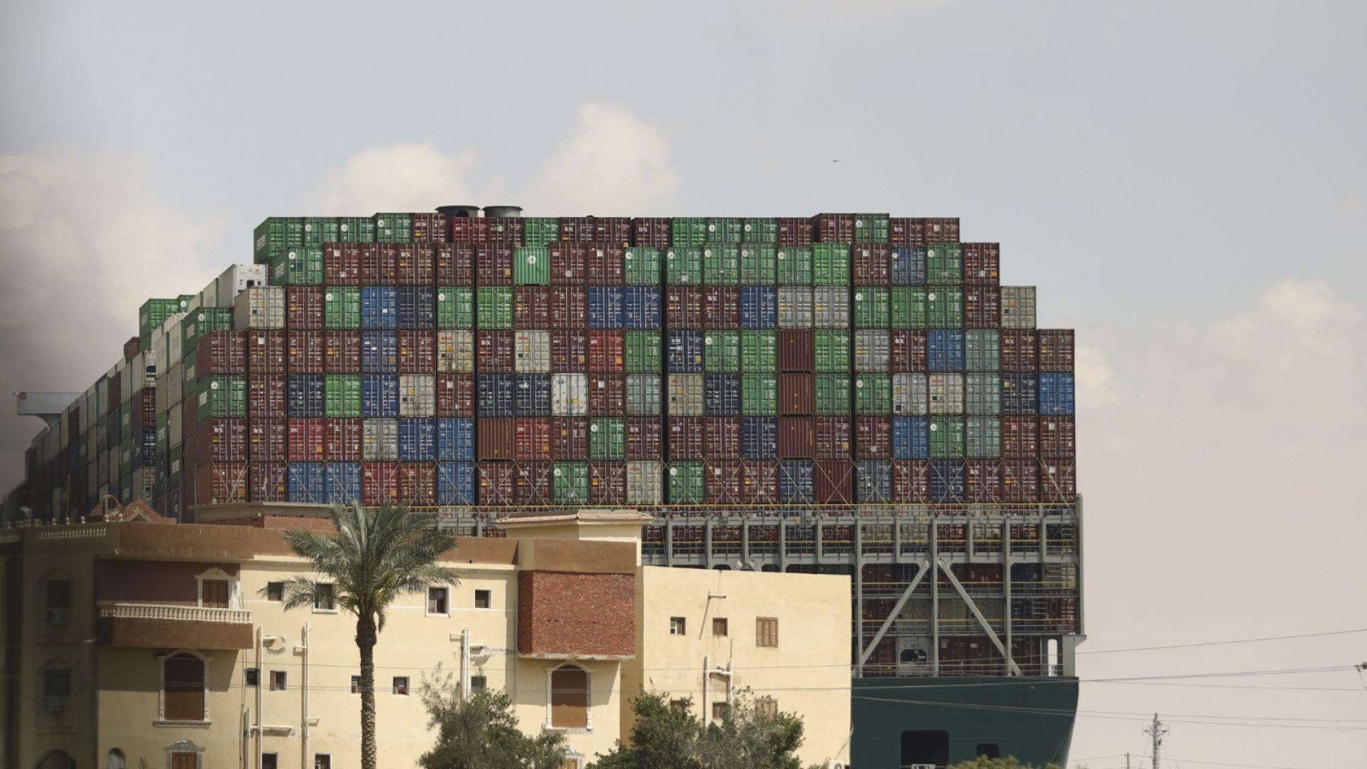 Корабът, долепен с единия си край до сграда на брега на канала