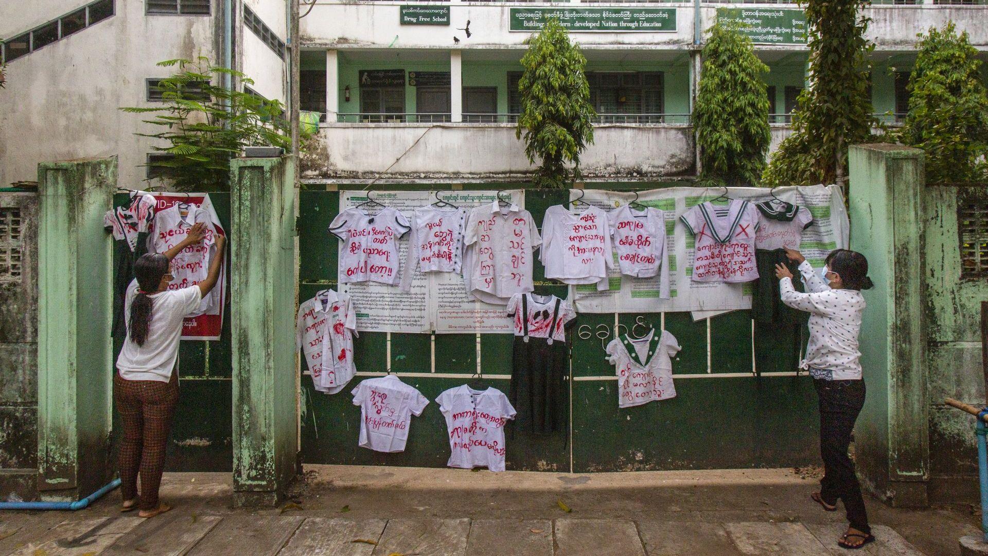 Активисти и протестиращи срещу преврата закачат ученически униформи на стената на училище по време на демонстрация