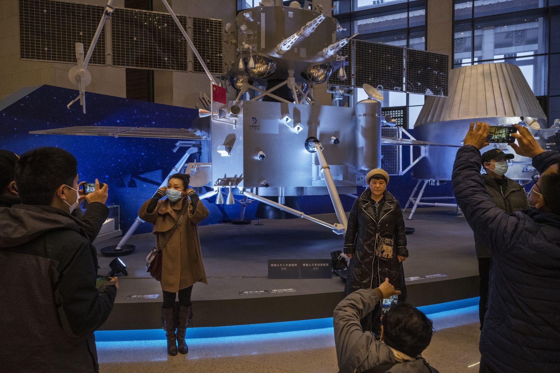 Посетители в Националния музей в Пекин разглеждат оборудването на китайската космическа програма. Благодарение на мисията на Китай на Луната, 40 години след кацането на САЩ, учените могат да изследват нови лунни скални проби. Китай влива милиарди в своята космическа програма, която има за цел да изпрати астронавти на Луната до 2030 г. (Photo by Kevin Frayer/Getty Images)