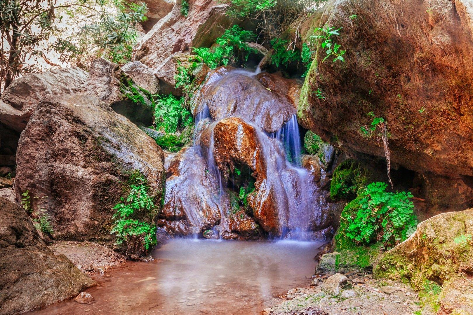 Водопадът, който тече в скалите до плажа