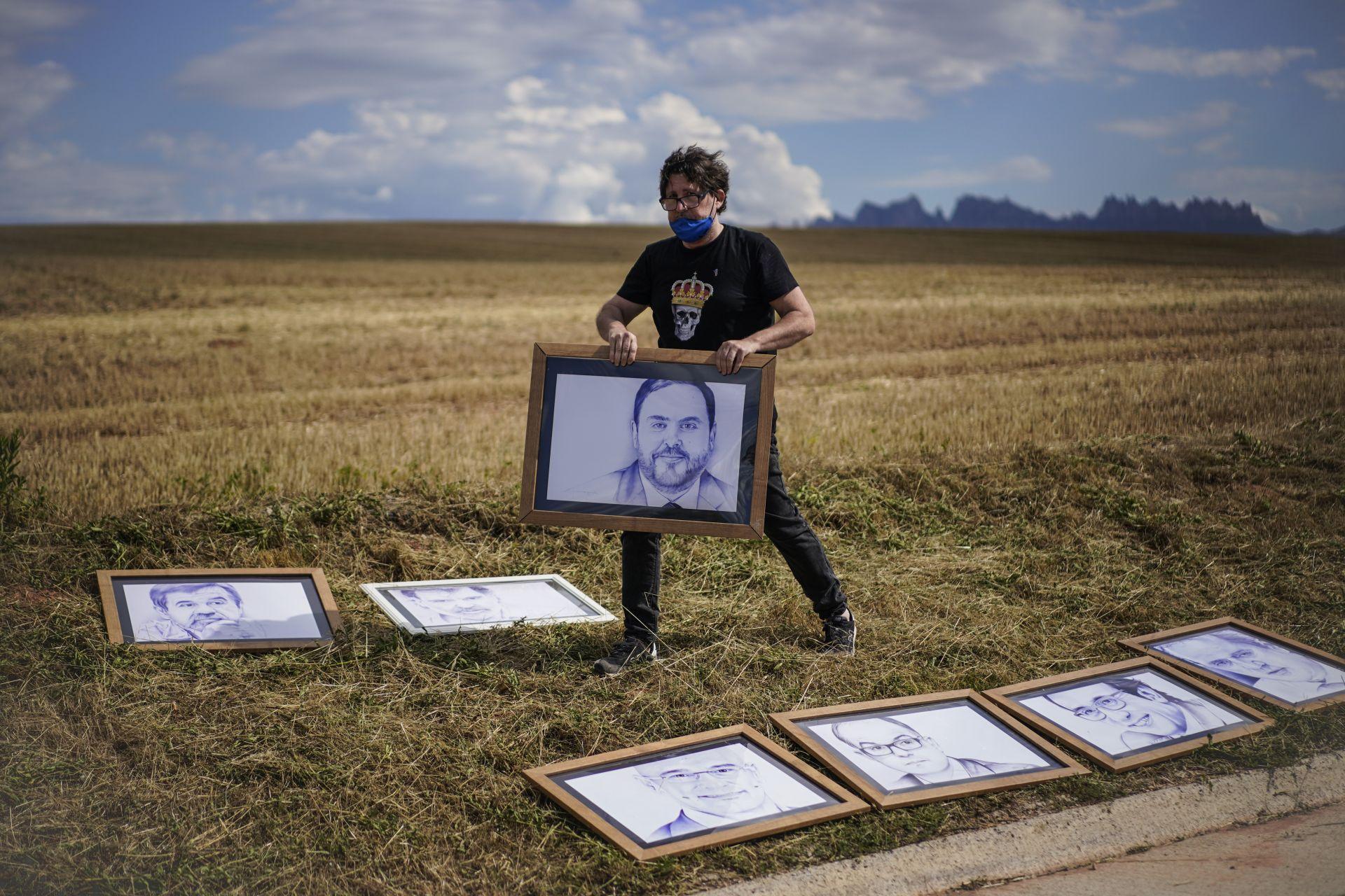 Мъж поставя рисунки на каталонските сепаратистки лидери, затворени за размирици пред затвора в Сант Джоан де Виларарада, близо до Барселона
