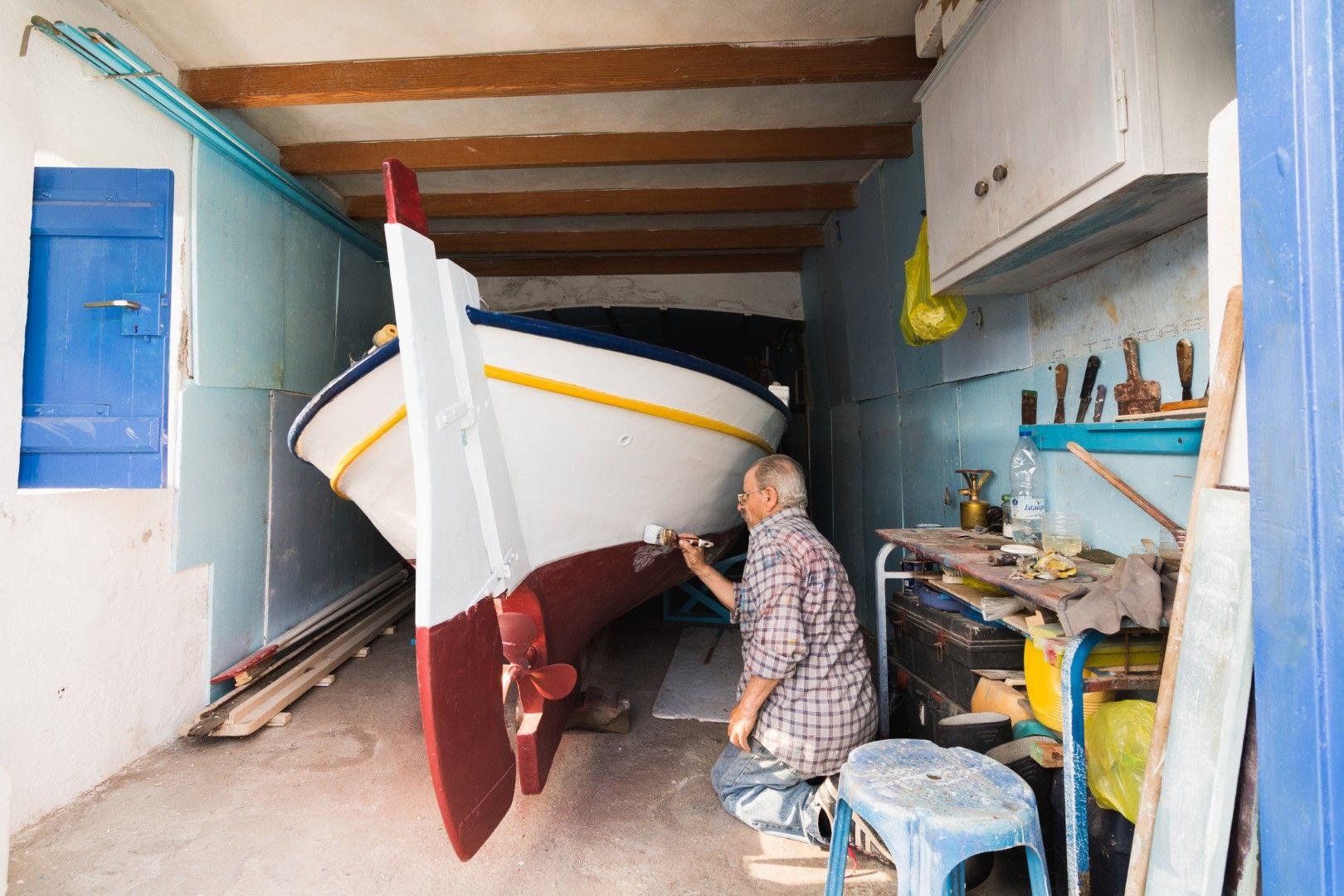 Рибар боядисва лодката си в гаража си в село Клима, Милос