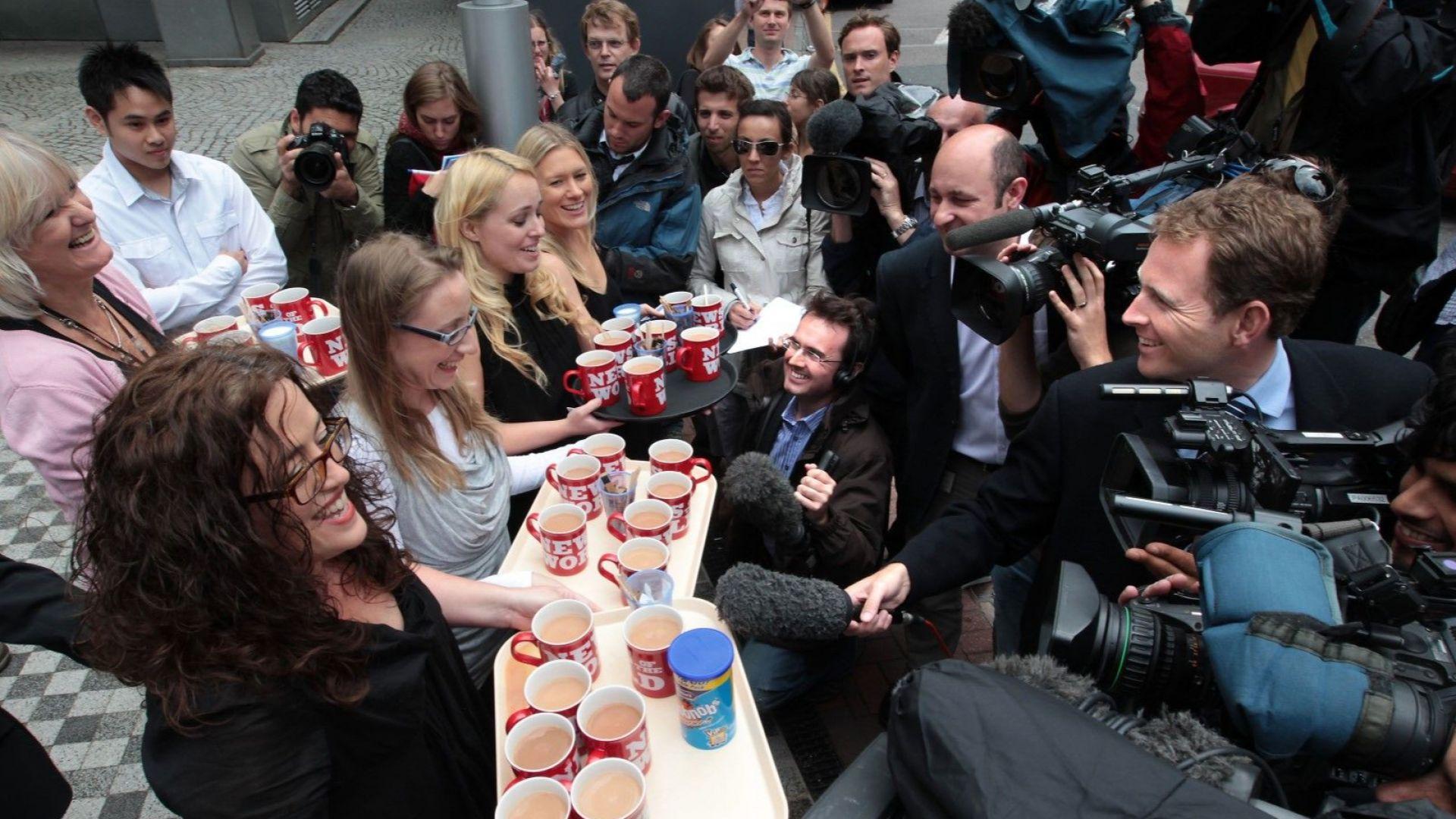 Служители на News of The World (от ляво) Хелън Мос, Франсин Пакър, Хана Ийдс и Джейн Хамилтън поднасят брандирани с логото на закрития вестник чаши чай на чакащите репортери пред офиса на News International на 9 юли 2011 г.