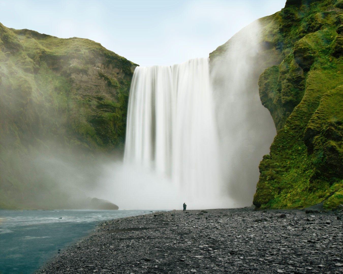Човек на фона на водопад Скогафос в Исландия.