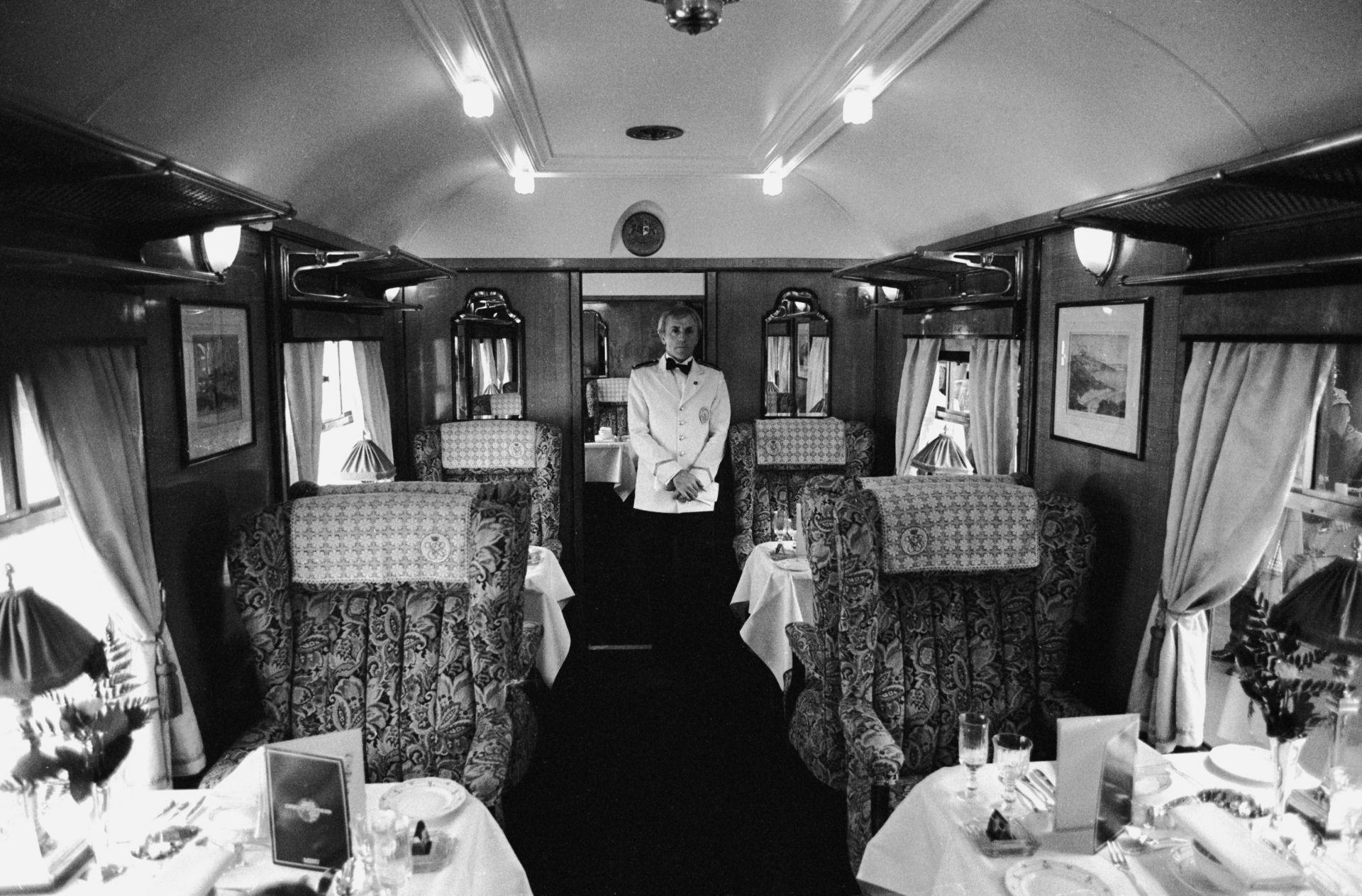 Барман подготвя чаши с вода за пътниците при отпътуването през май, 2000 година