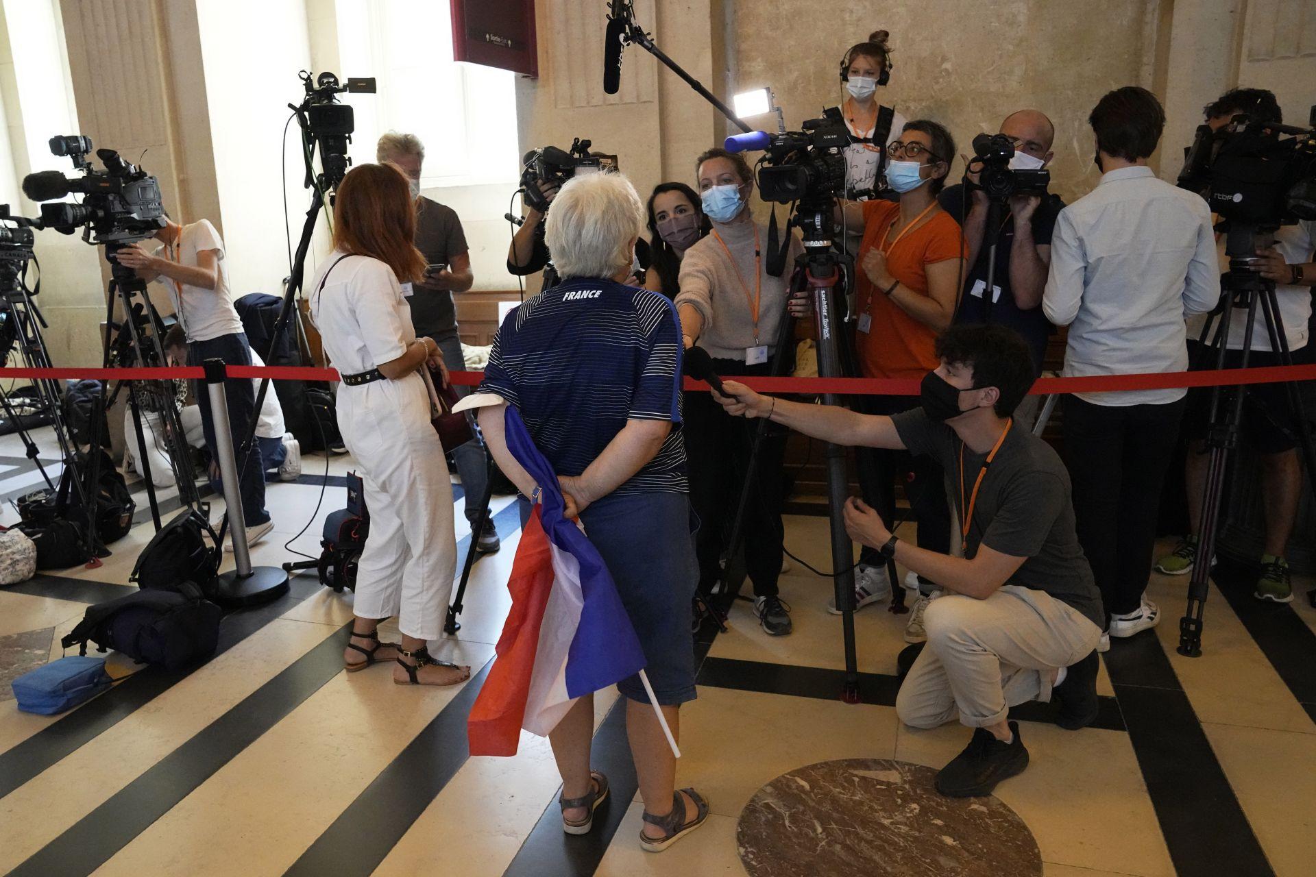 Участник в процеса по атаките, държащ френско знаме, отговаря на репортерите, когато пристига в специалната съдебна зала в сряда