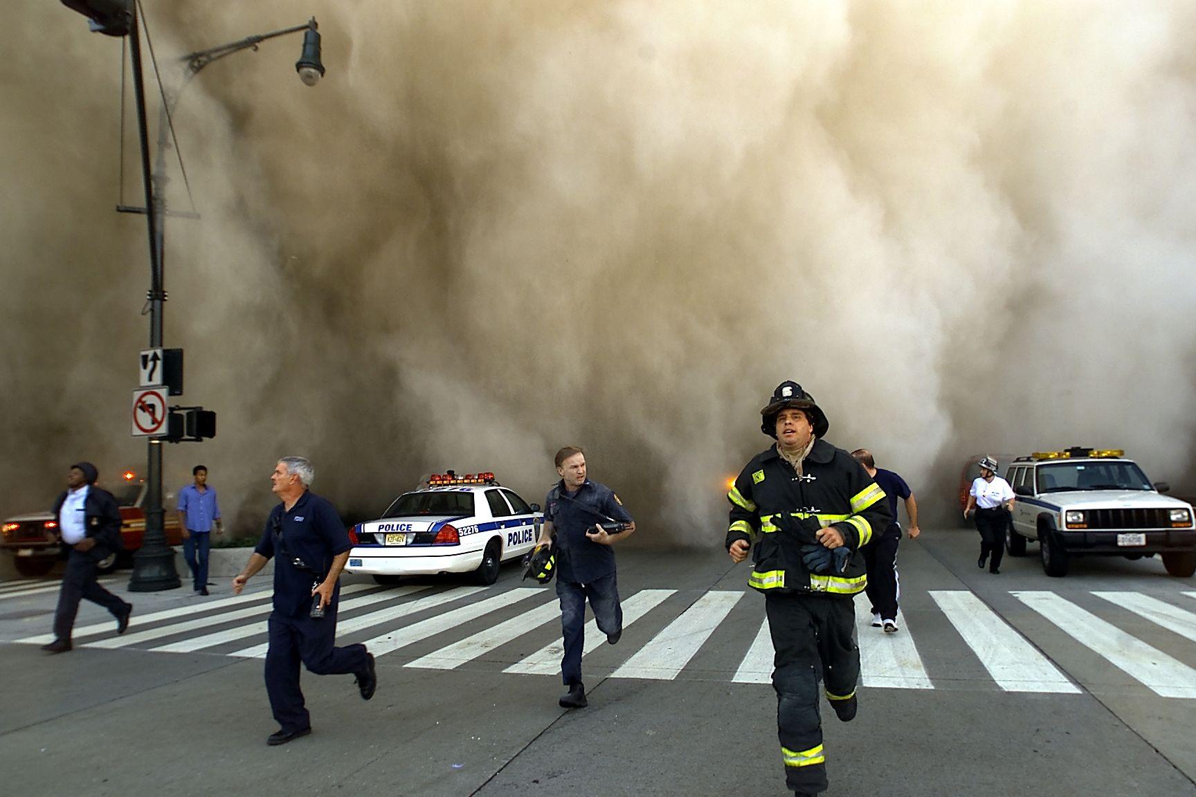 Полицаи и пожарникари бягат от огромния облак прах