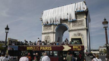 Туристи наблюдават последния етап от опаковането на Триумфалната арка в Париж (снимки)